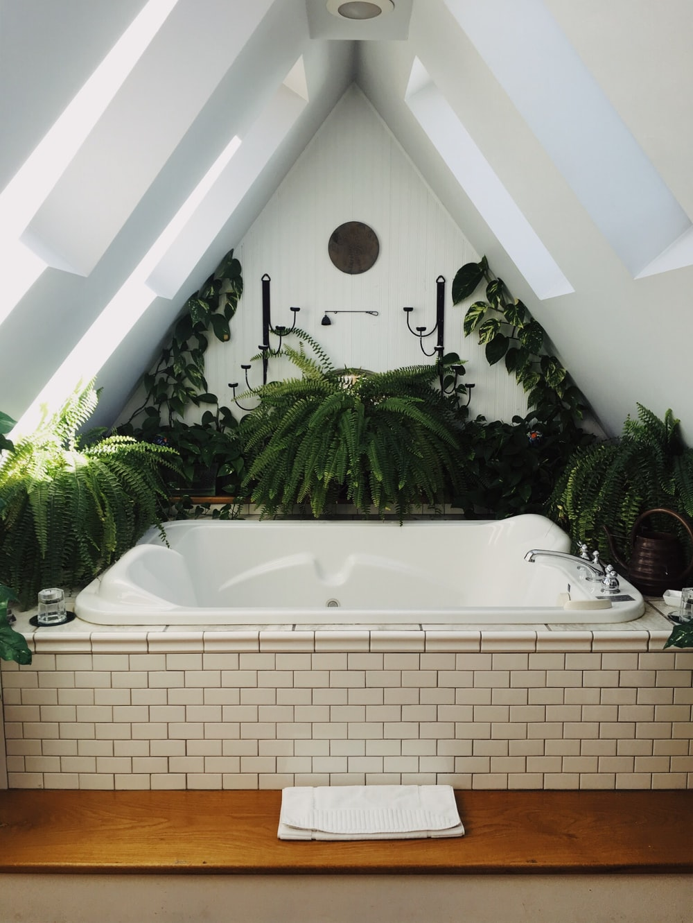 white bathtub surrounded with flowers