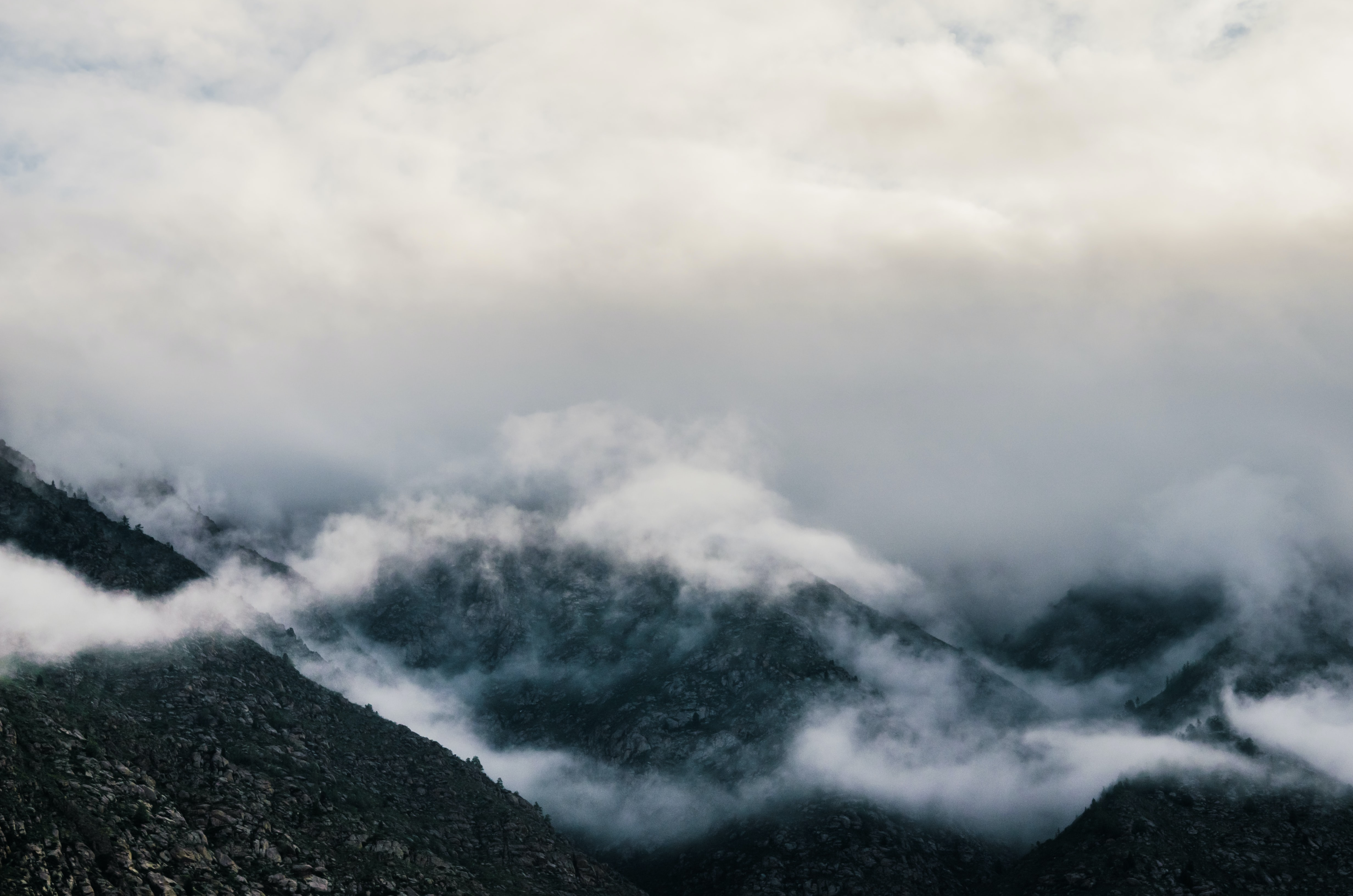 bird's eye view of mountains surrounded by fogs