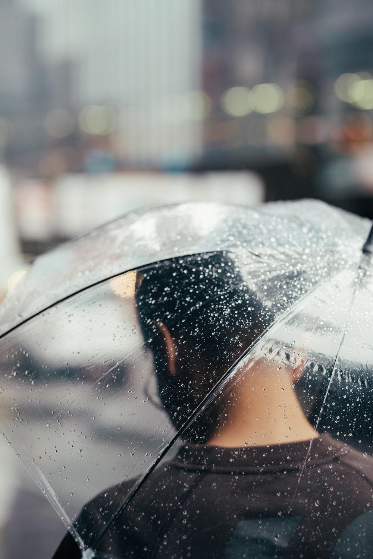 selective focus photography of person under transparent umbrella