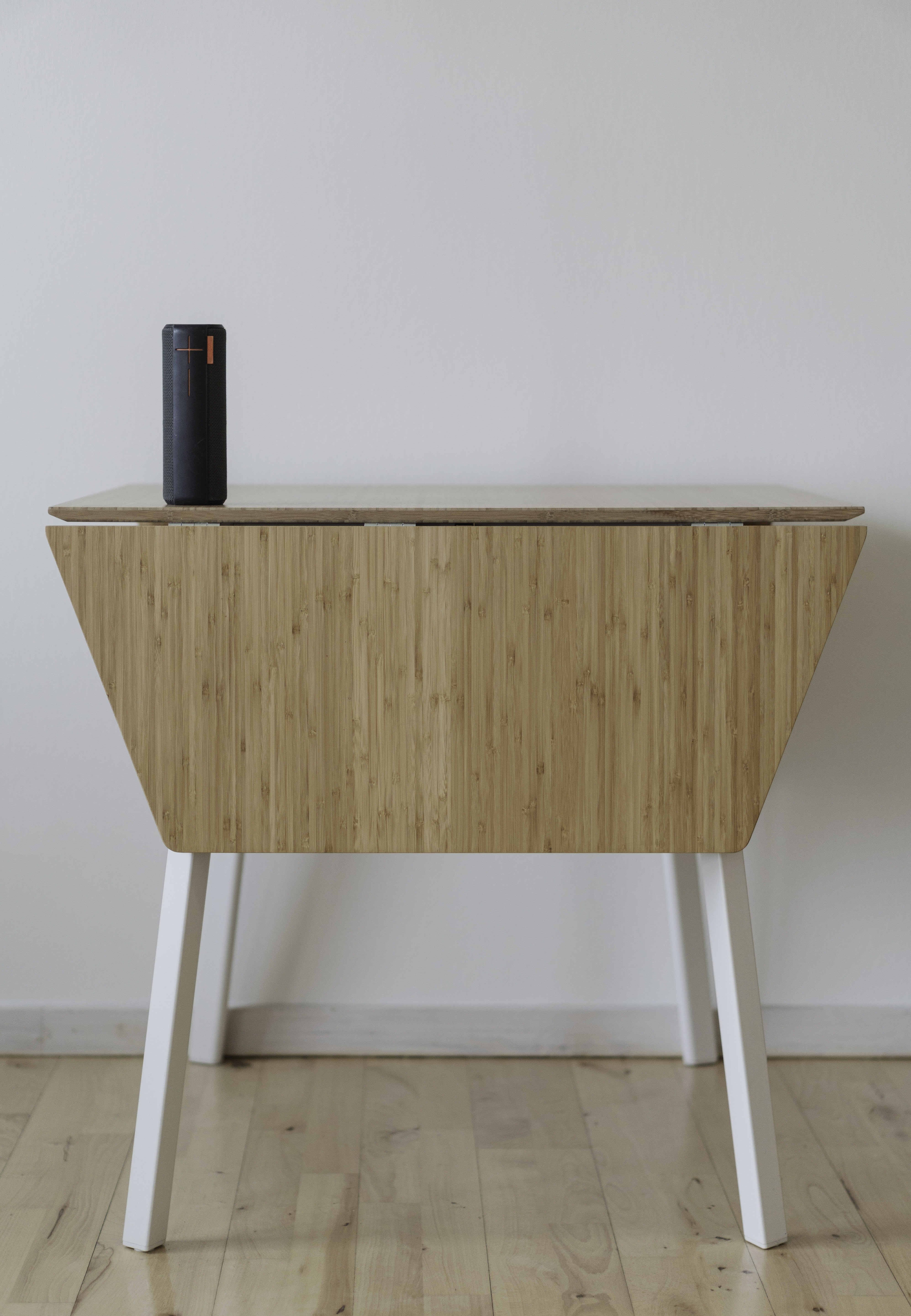 black Bluetooth speaker on top of brown wooden drop leaf table