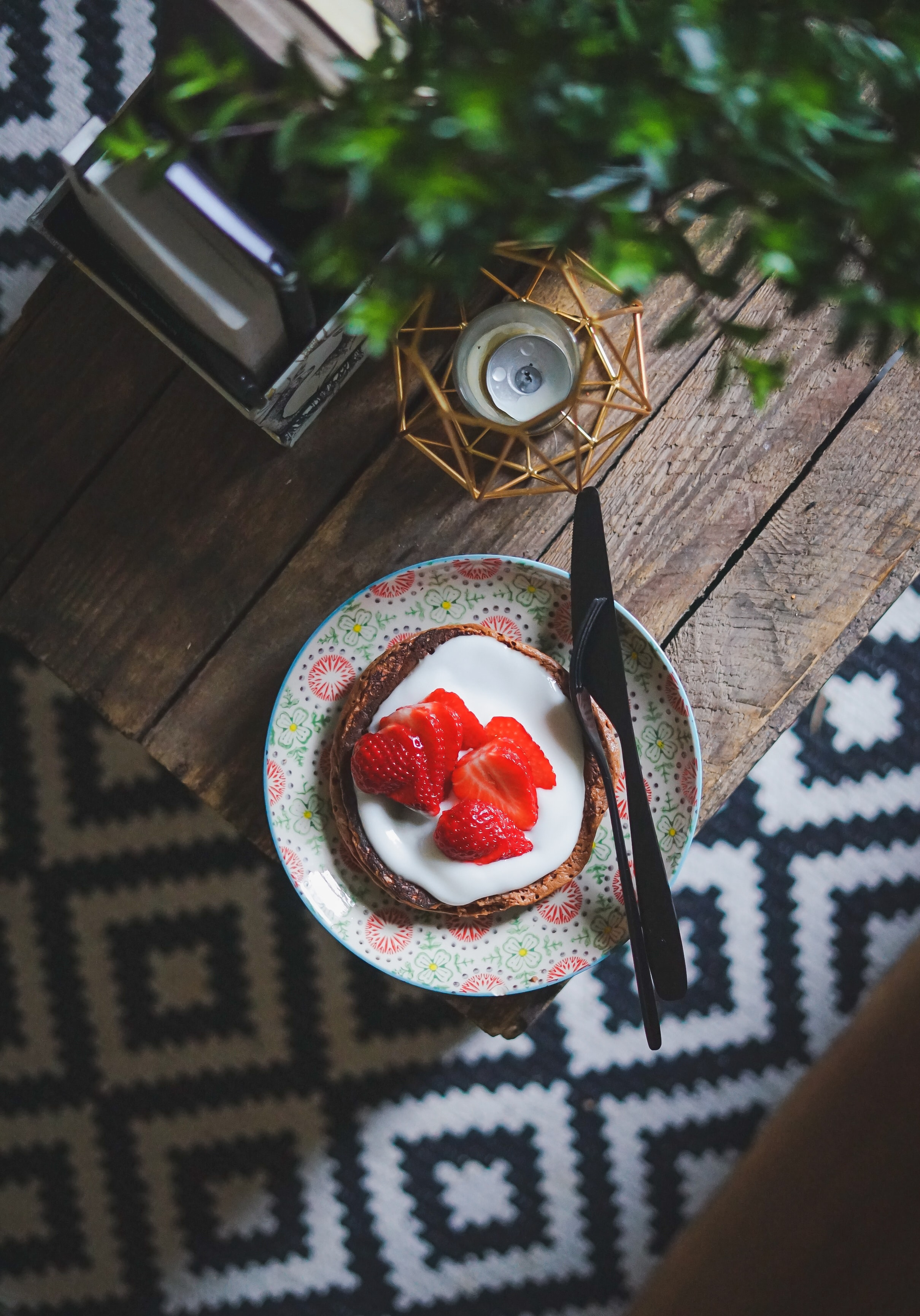 chocolate pancake with cream and strawberry beside fork and knife
