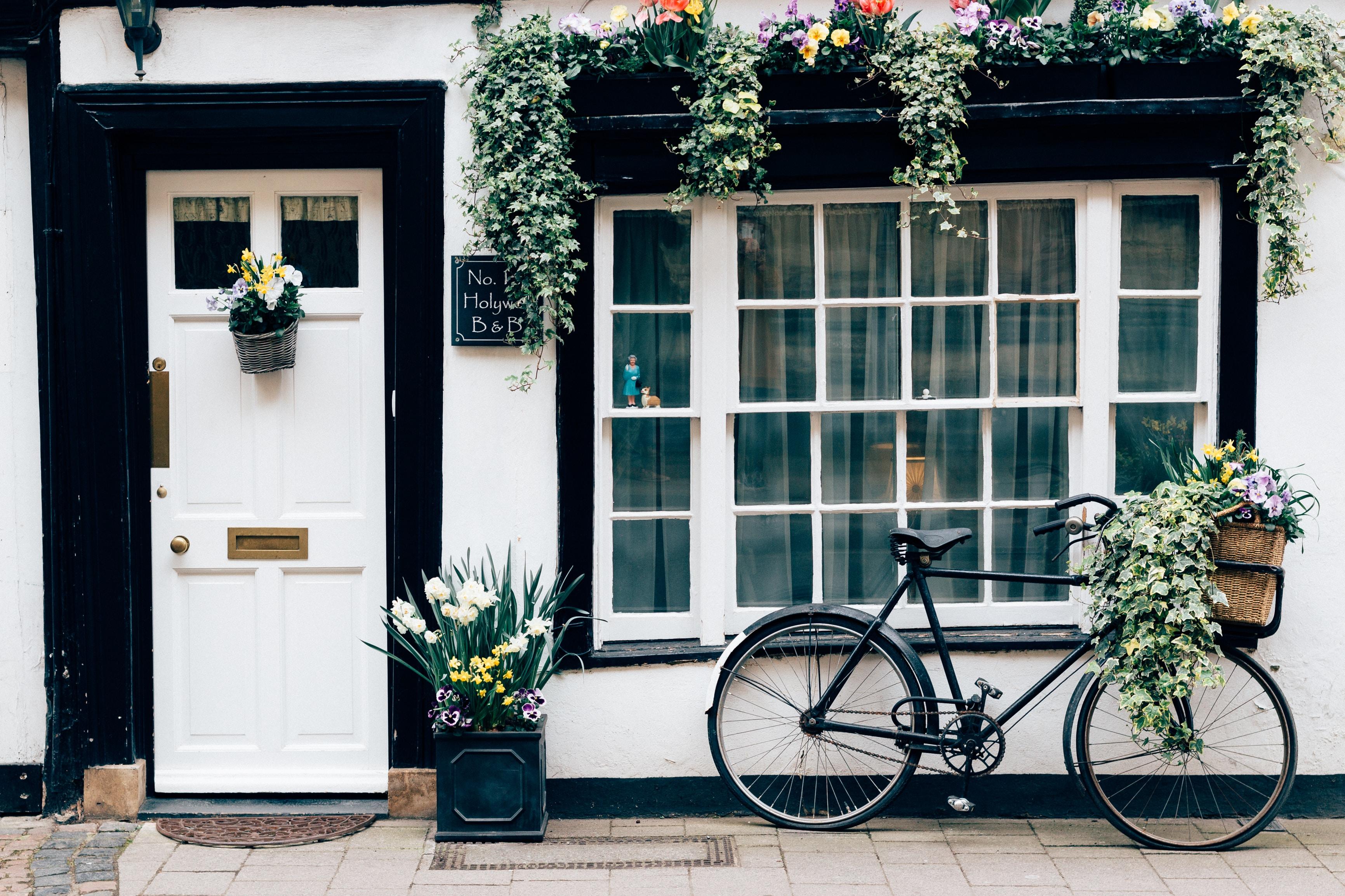black fixie bike near white wooden door