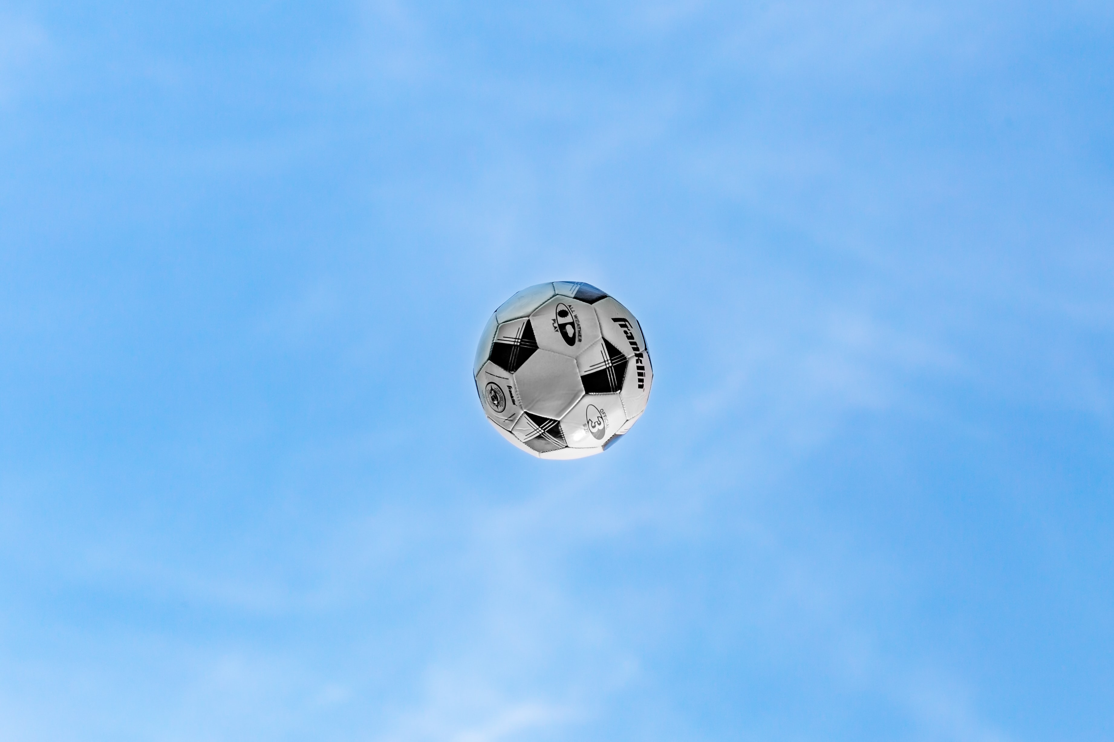 white and black soccer ball on air