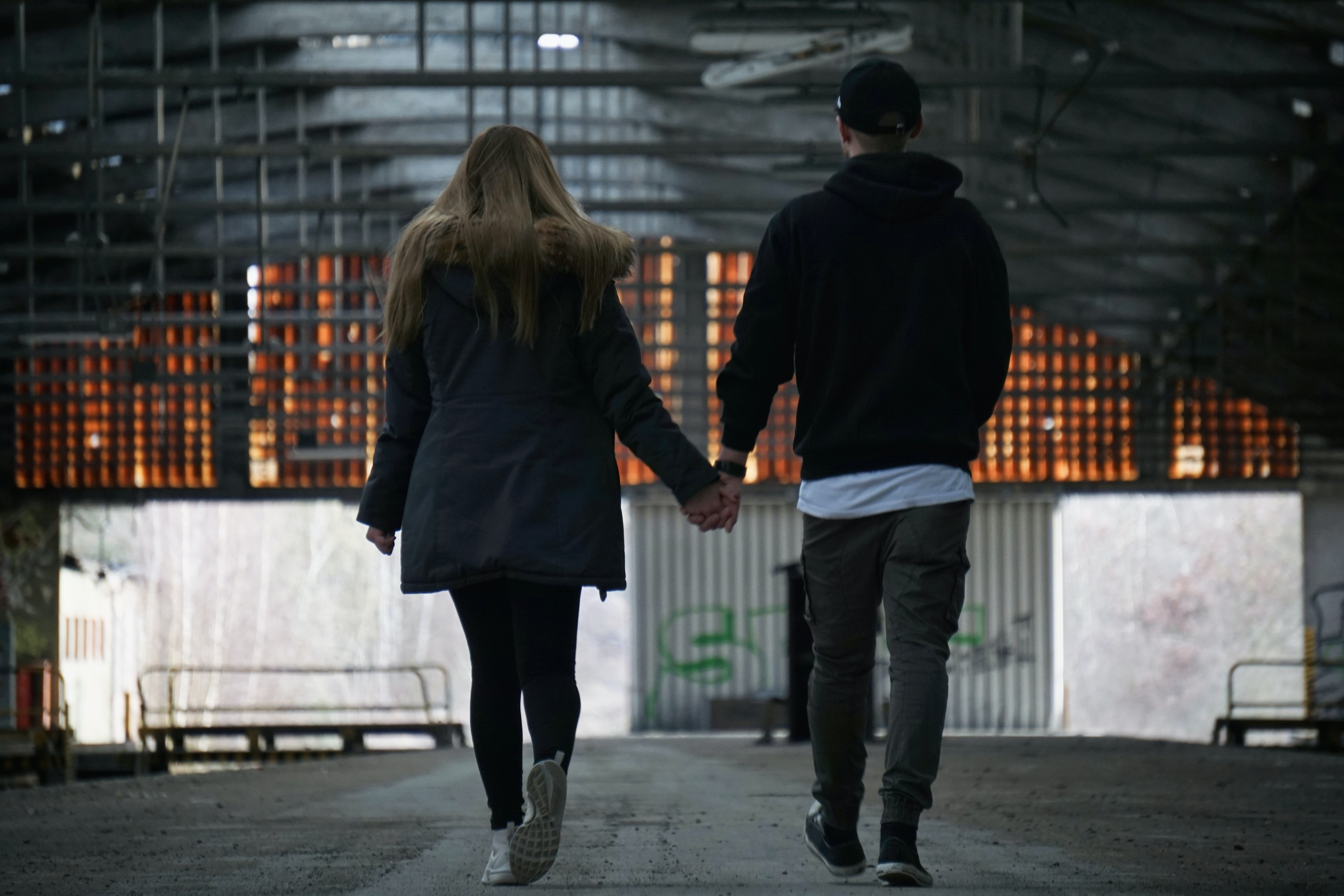 man and woman walking while holding hands