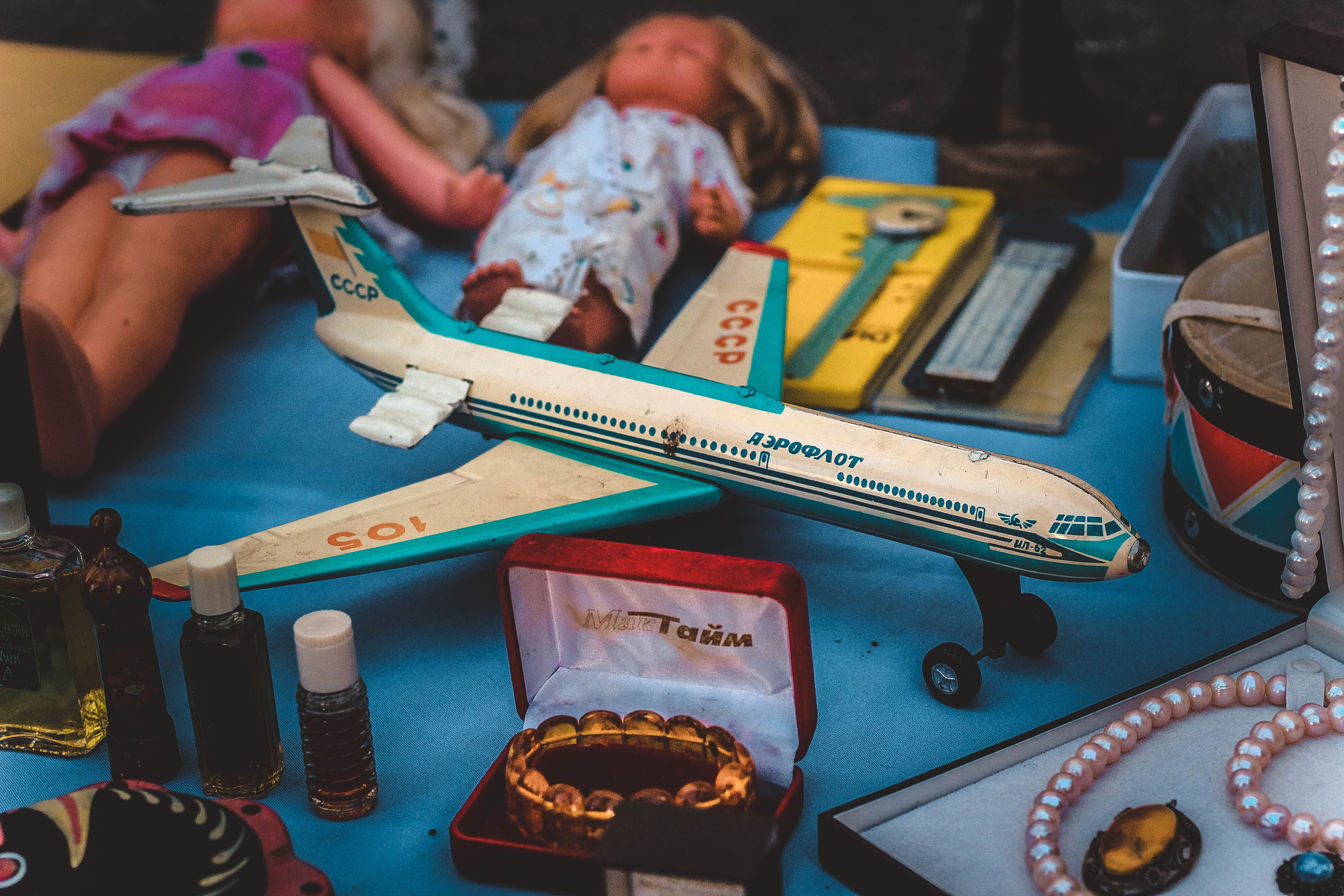 closeup photo of airplane scale model and jewelry
