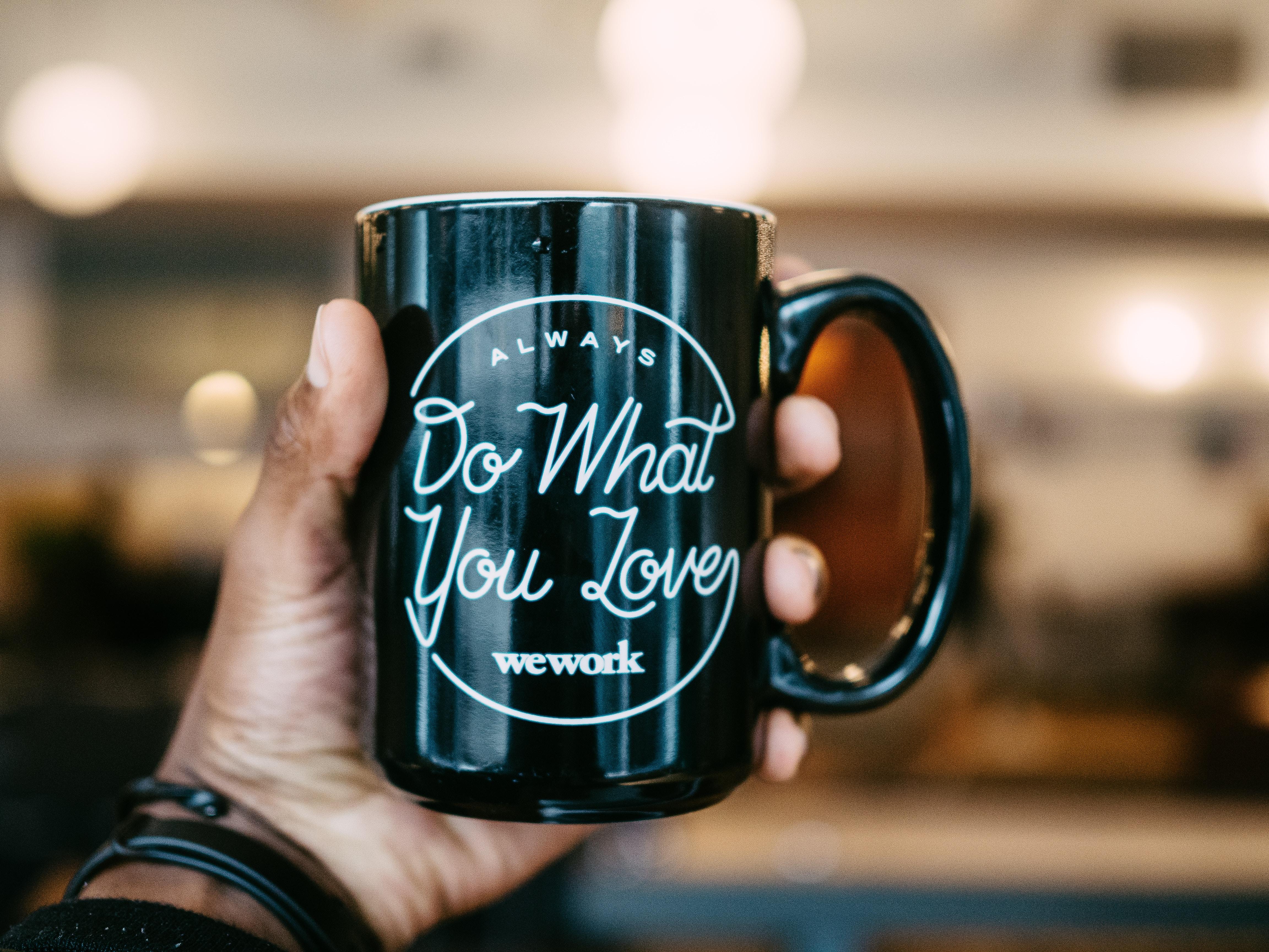 shallow focus photo person holding black ceramic mug