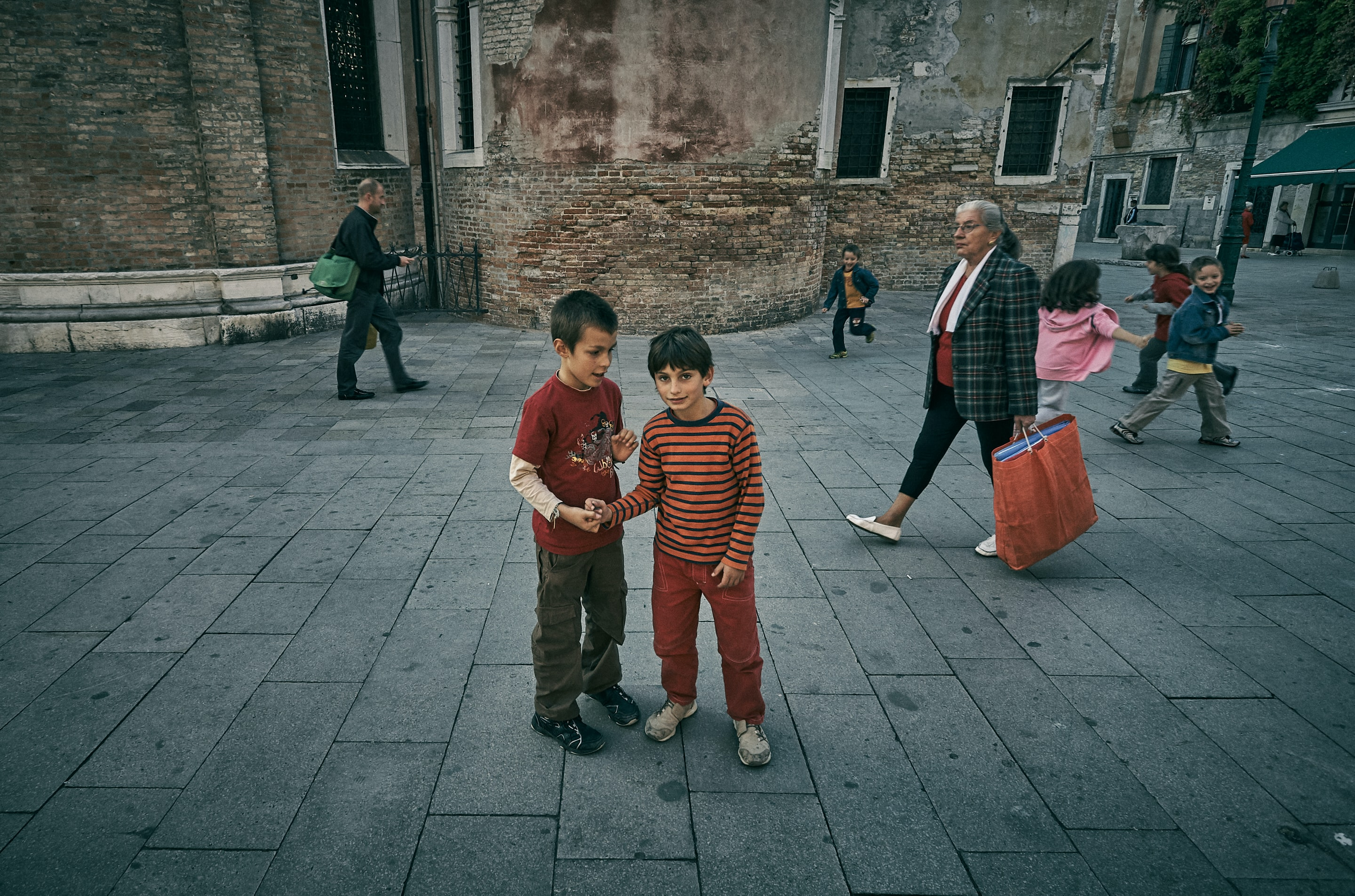 two boys standing in-front building