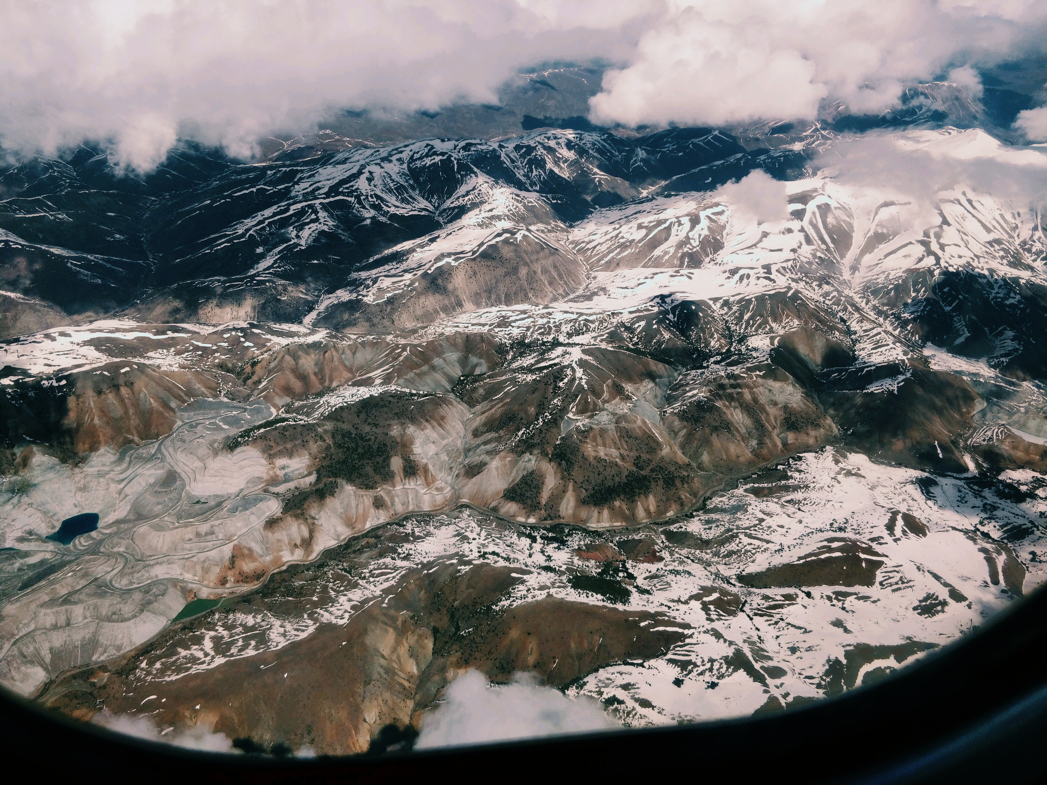 plane window showing snow filled moutain