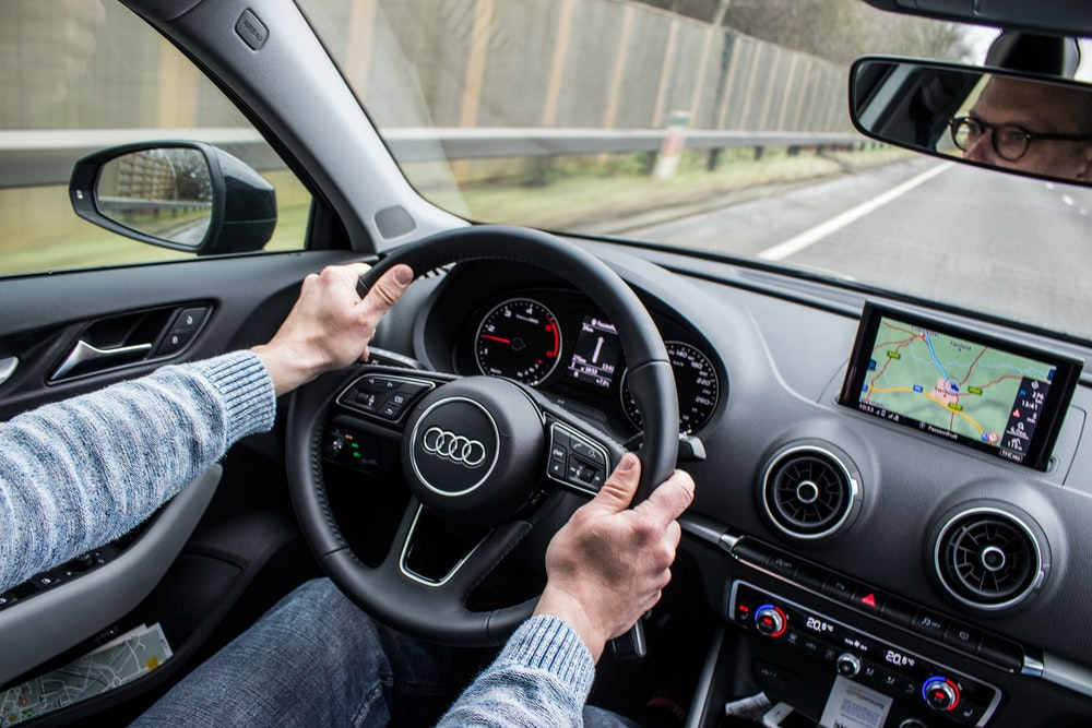 man driving Audi car on asphalt road