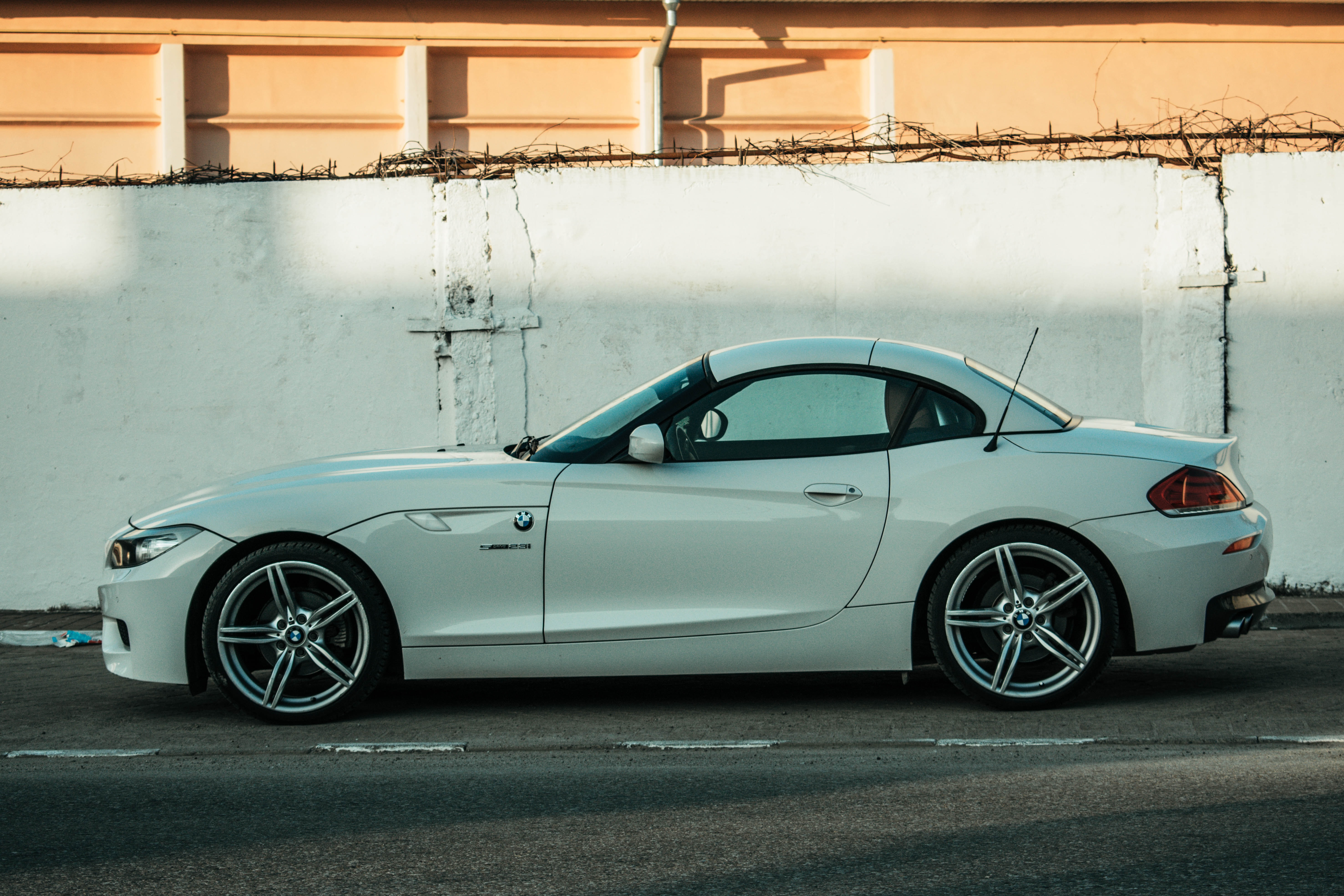 white coupe parked beside white concrete wall