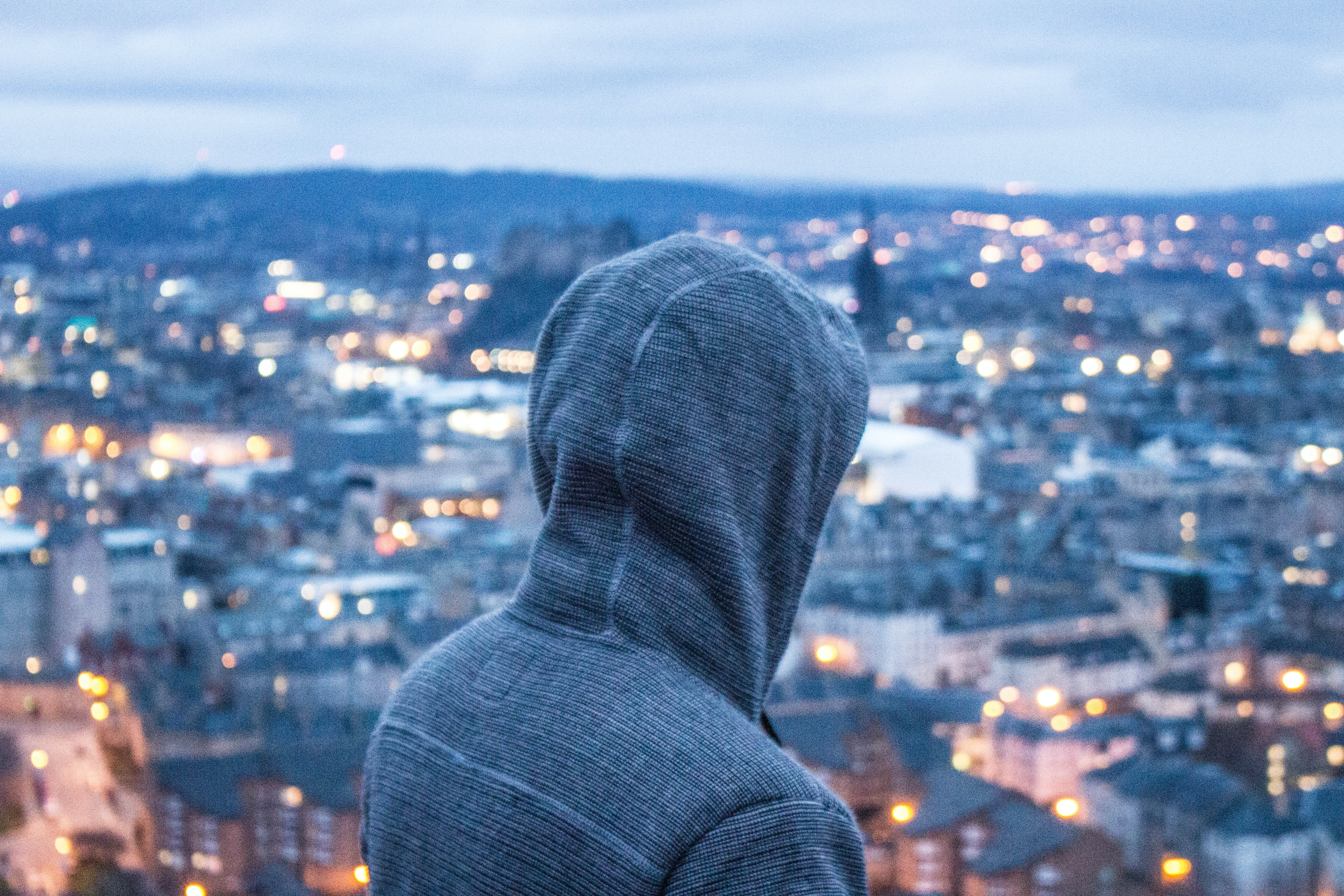 person wearing gray hoodie standing while facing aerial view of city