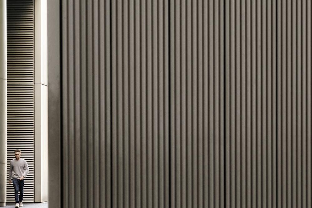 man walking towards gray wall