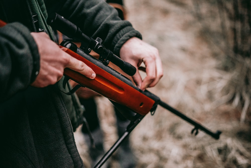 person loading brown and black sniper rifle