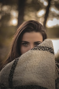 woman covering her face with brown cloth