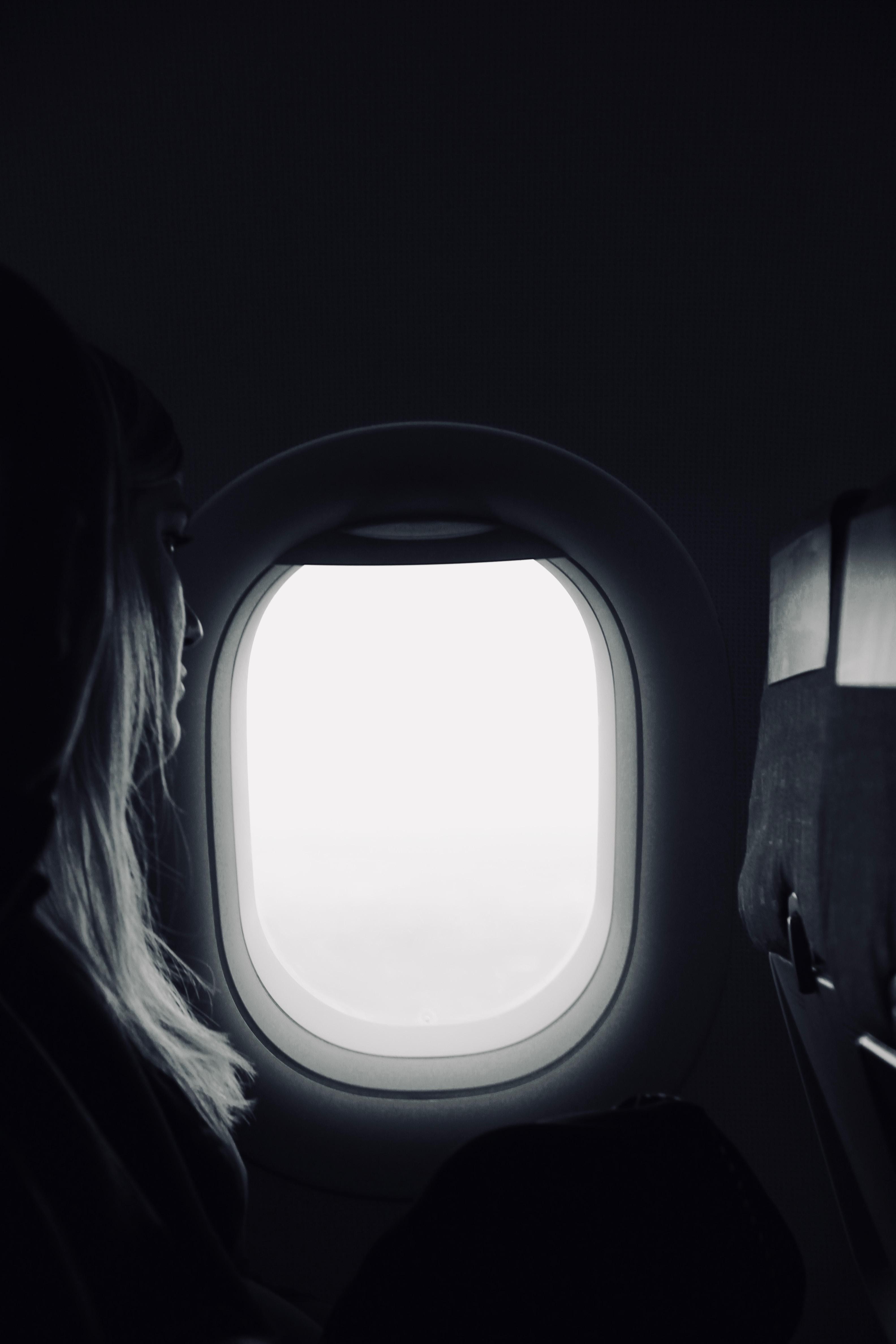 person sitting beside airplane window