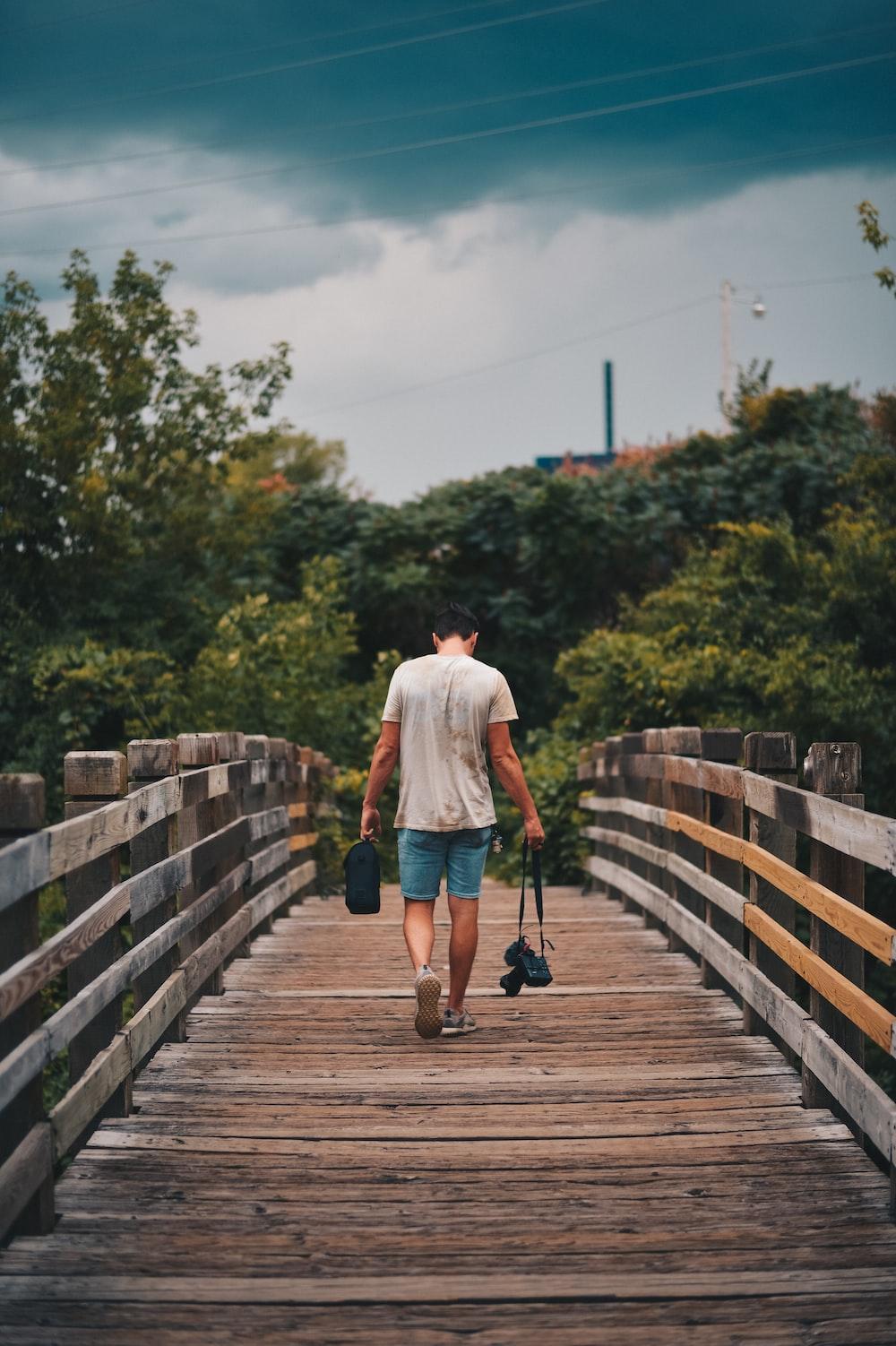 man walking on brown wooden bridge