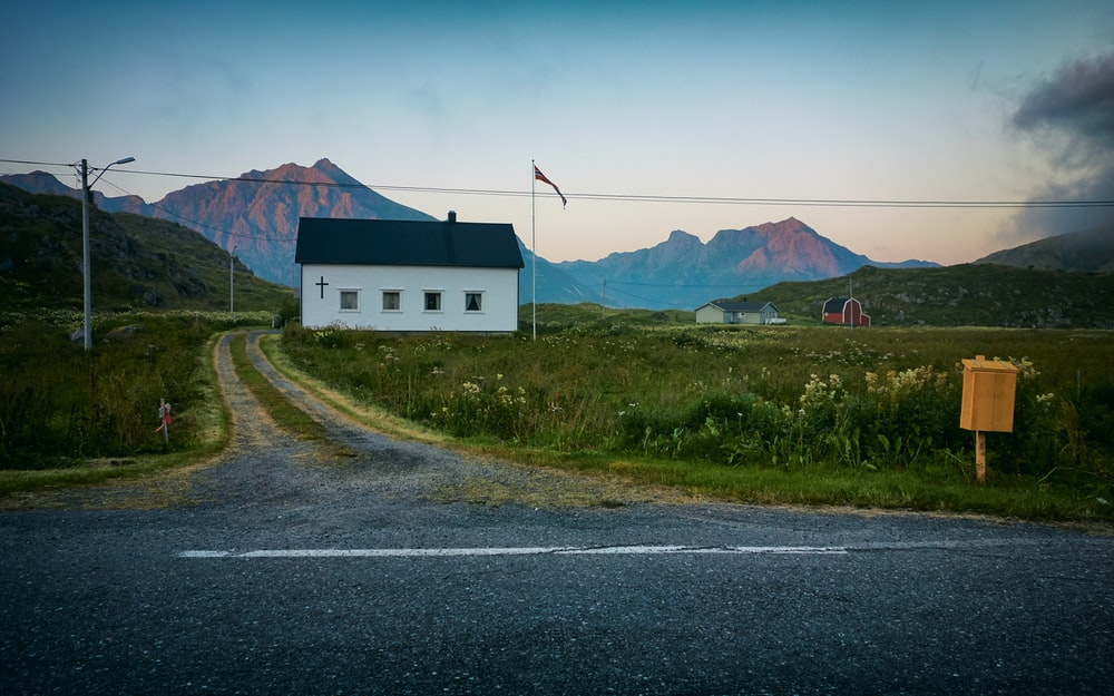 white and black wooden house near farm