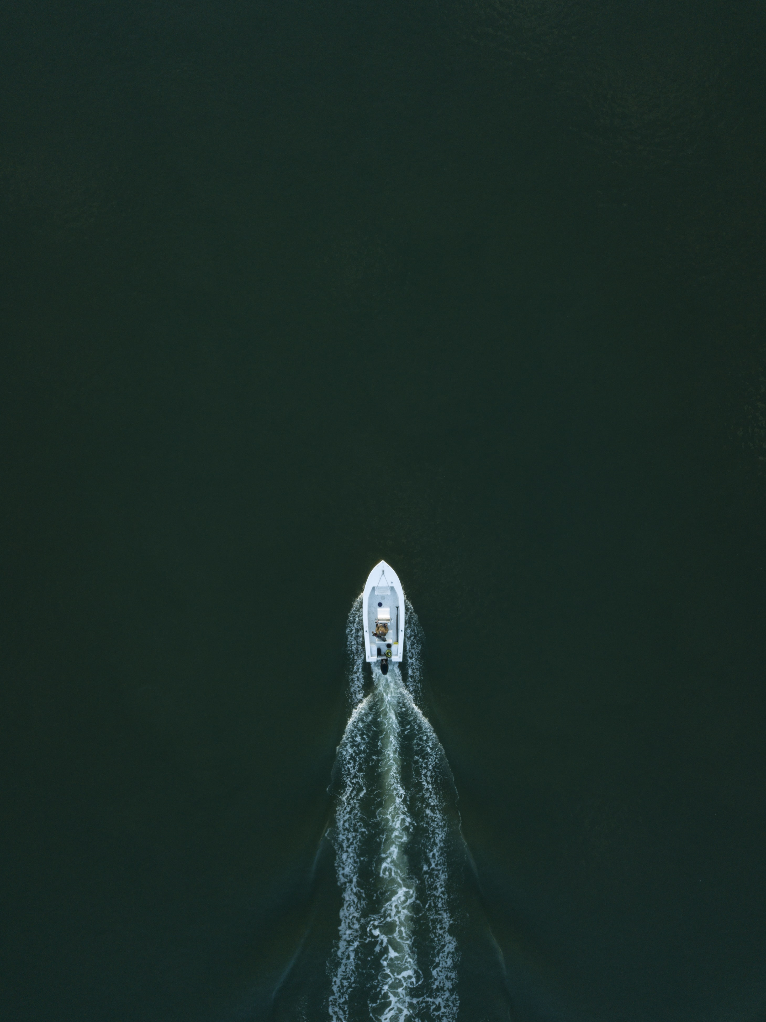 white powerboat at body of water leaving water trail