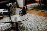 square clear glass-top coffee table on gray area rug