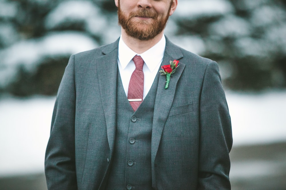 man wearing gray notched lapel blazer, gray waistcoat, and white dress shirt with rose buttonaire