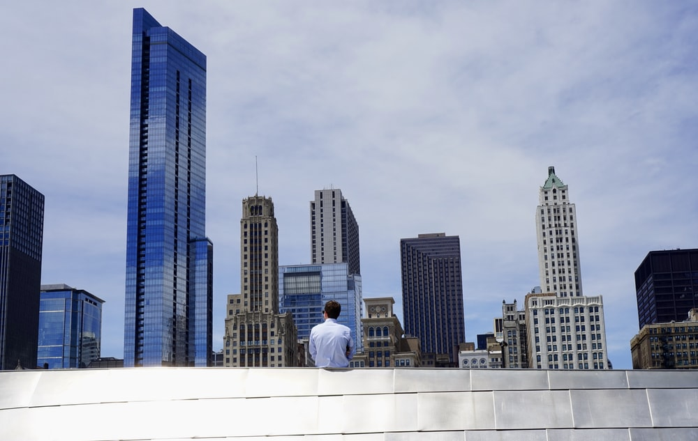 photography of man sitting on roof while looking at city buildings