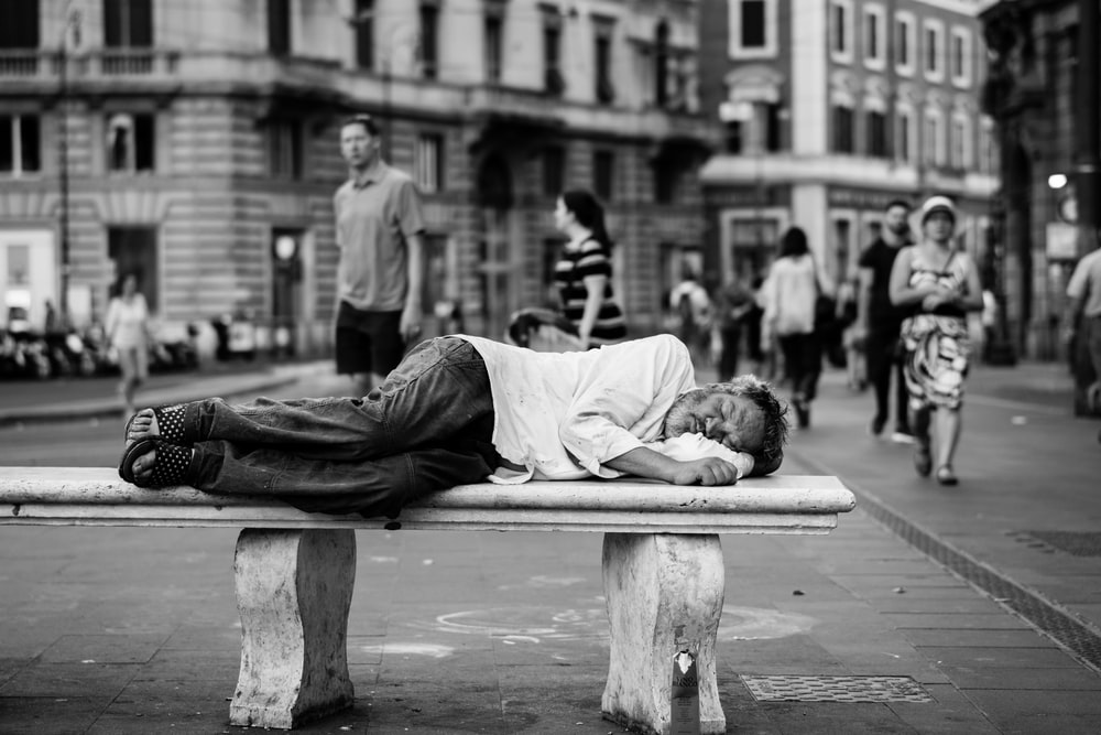 man sleeping on bench in the middle of the street