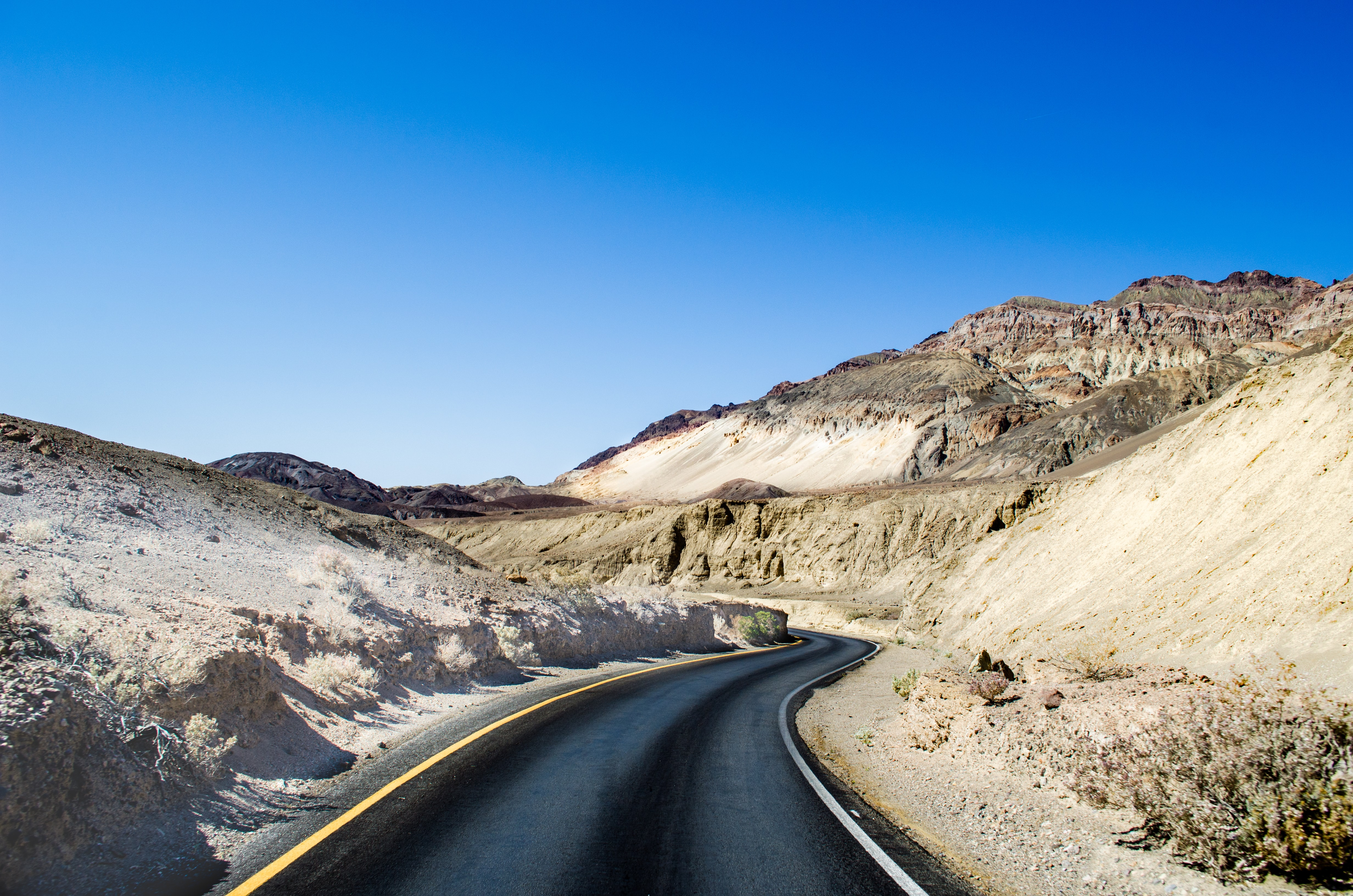 empty roadway between mountains under blue sky at daytime