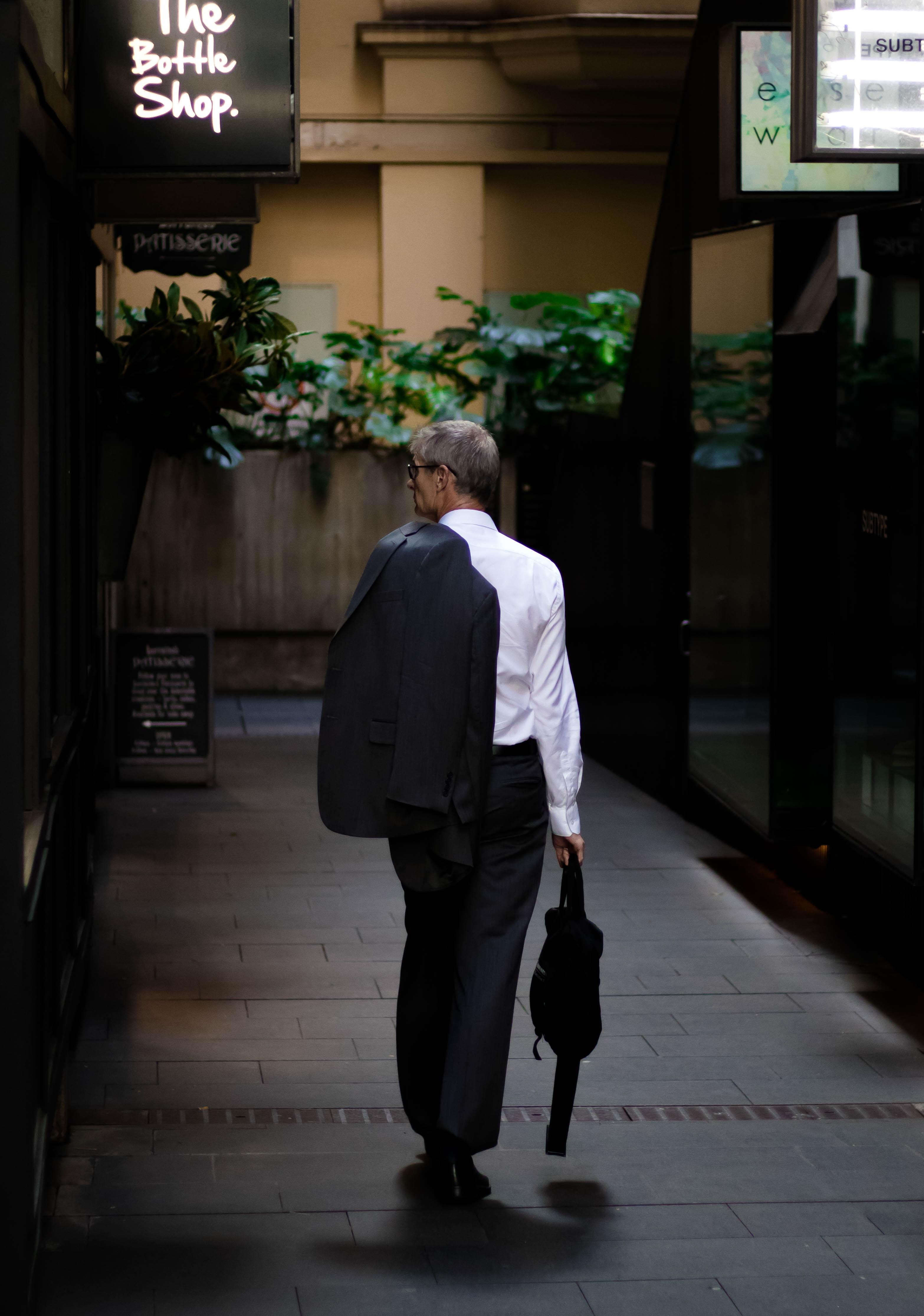 man holding black bag walking on road