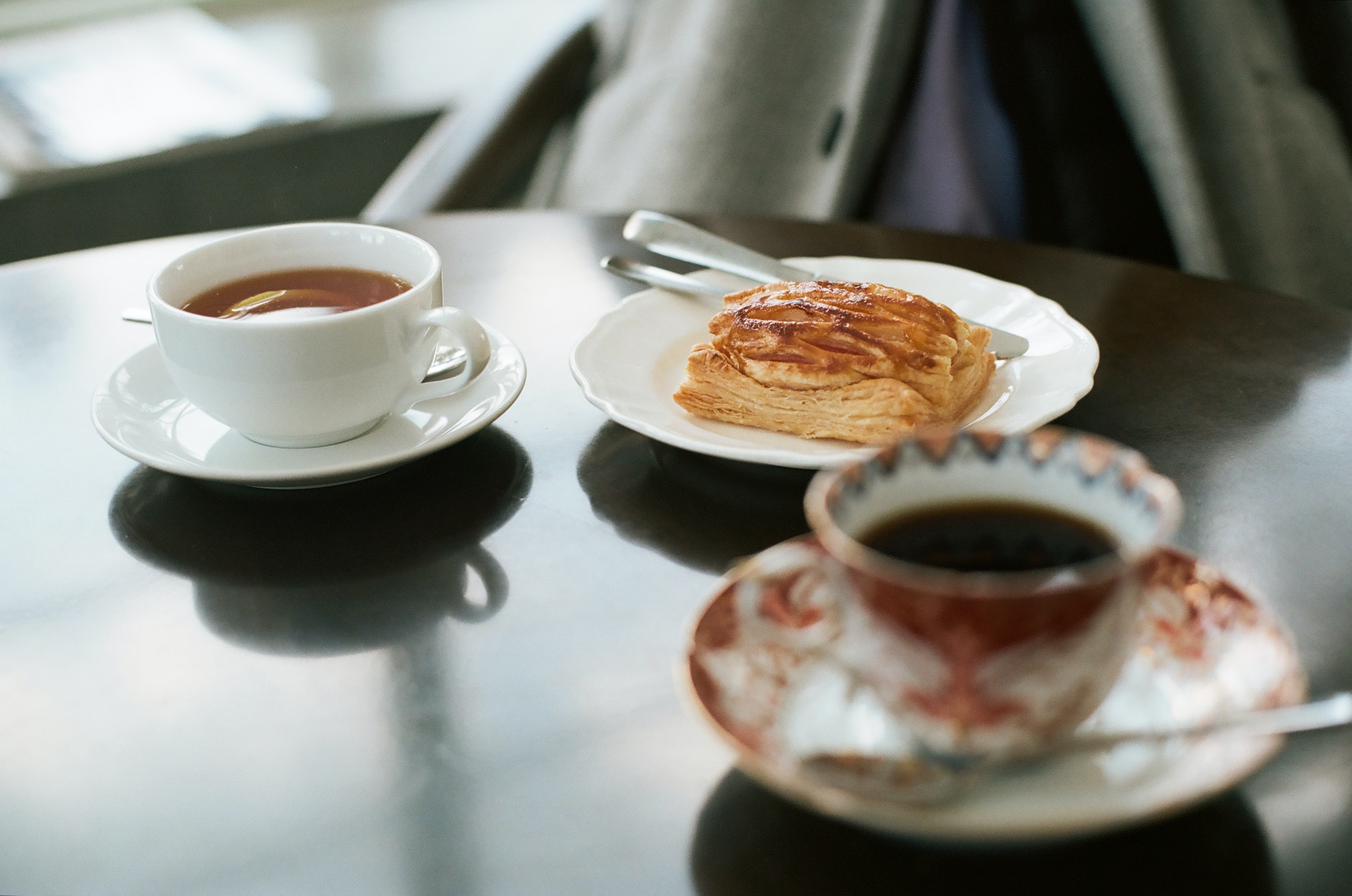 bread on ceramic plate near white ceramic teacup filled with coffee