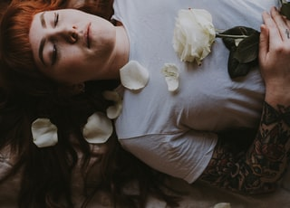 woman sleeping holding white rose flower