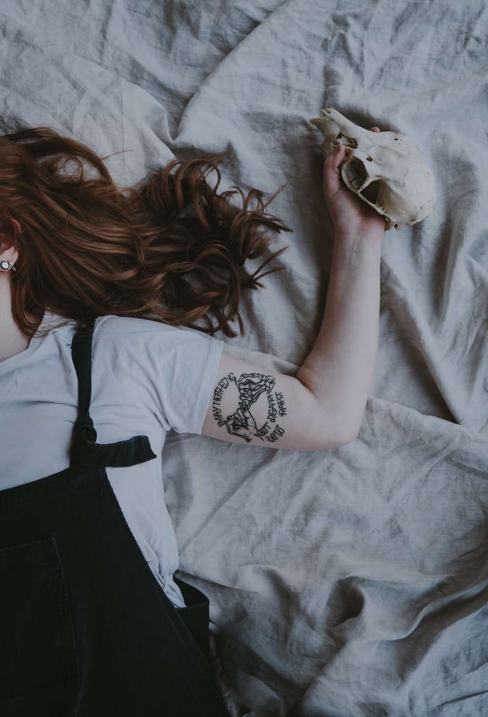 woman laying on gray bed with left arm tattoo