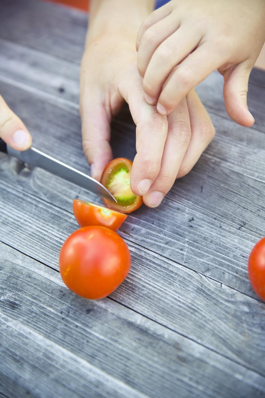 person slicing tomatoe