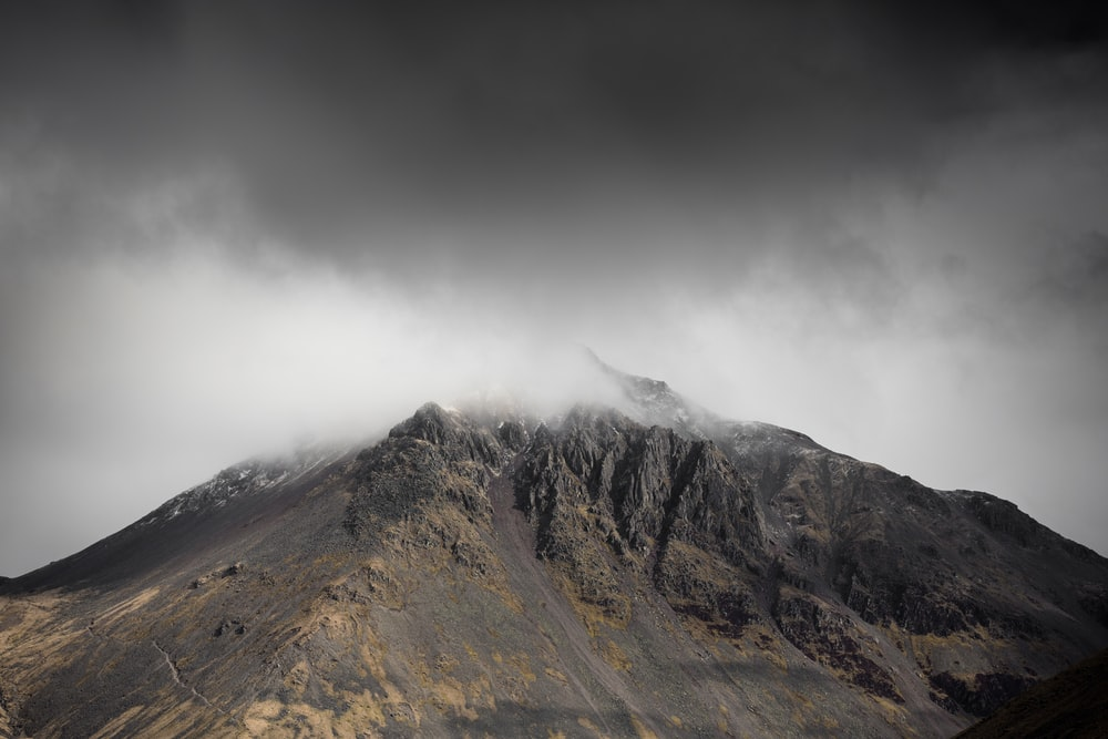 brown mountain with white clouds