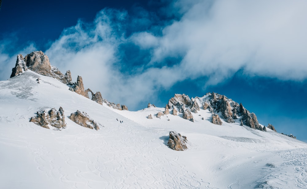 snow-covered rock mountain under clods