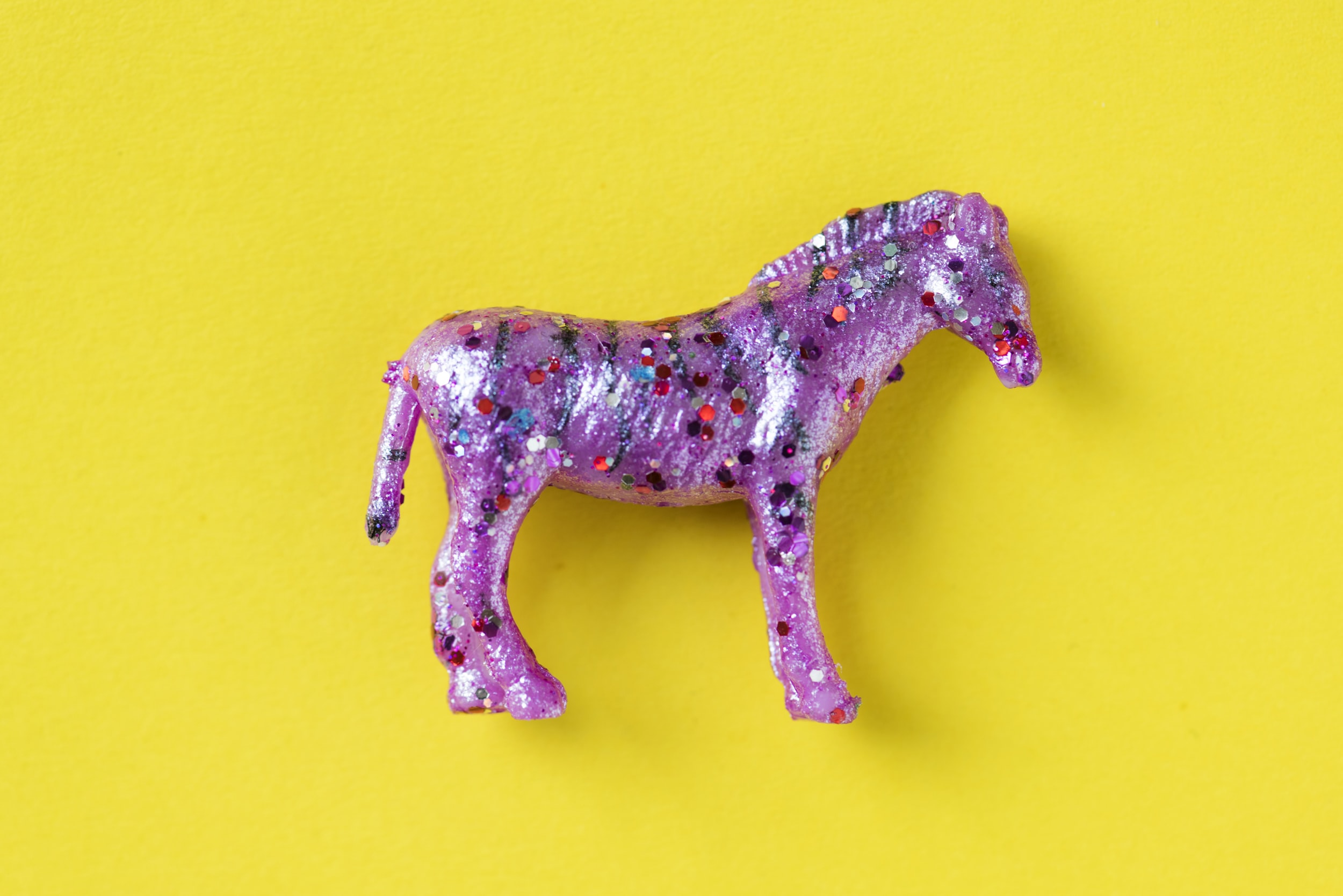 pink horse figurine on yellow surface