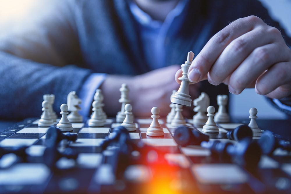 depth of field photography of man playing chess