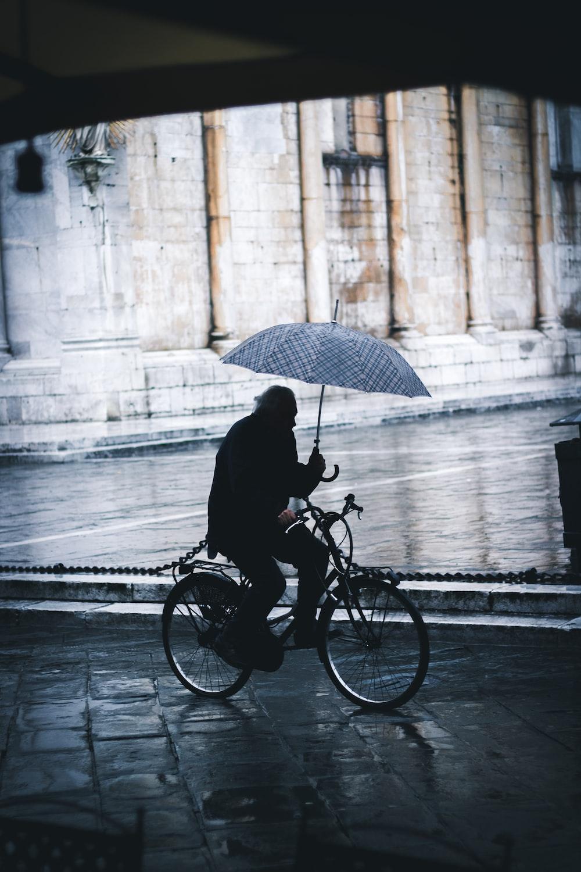 man riding bicycle while holding umbrella near street