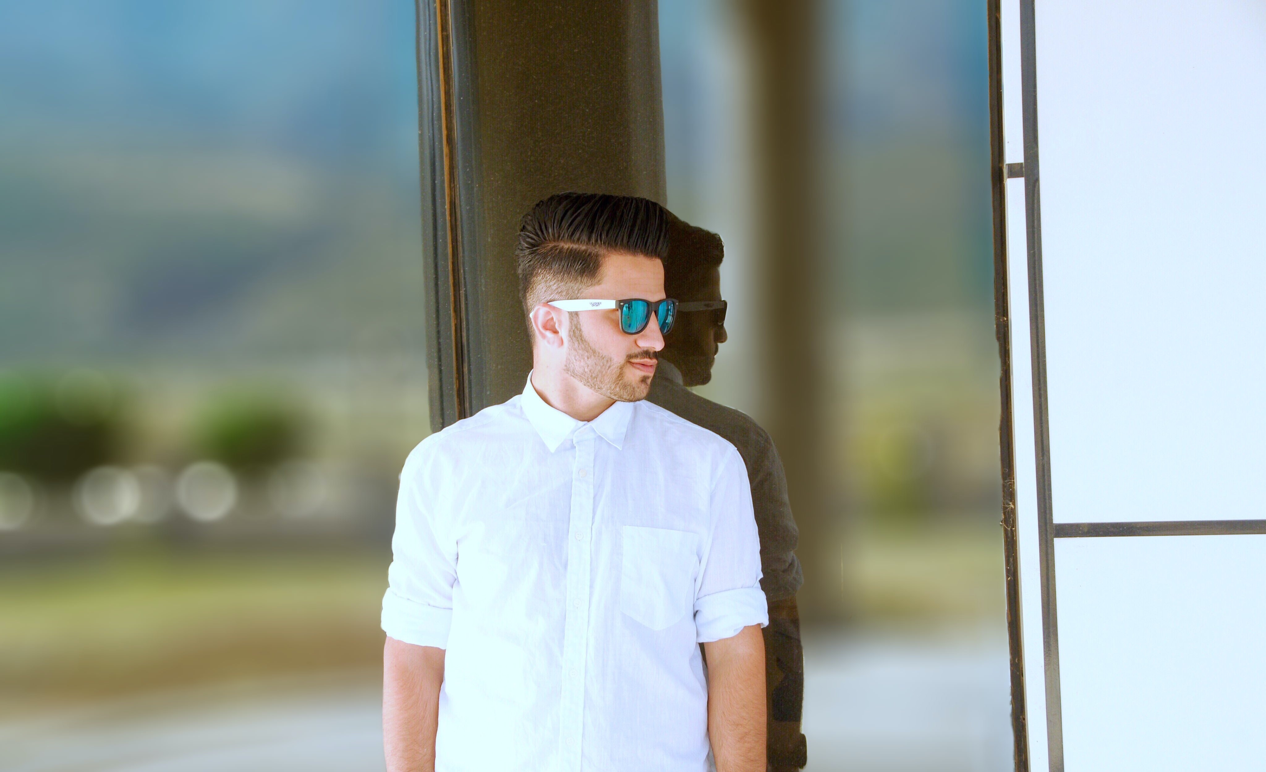 man leaning on glass wall during daytime