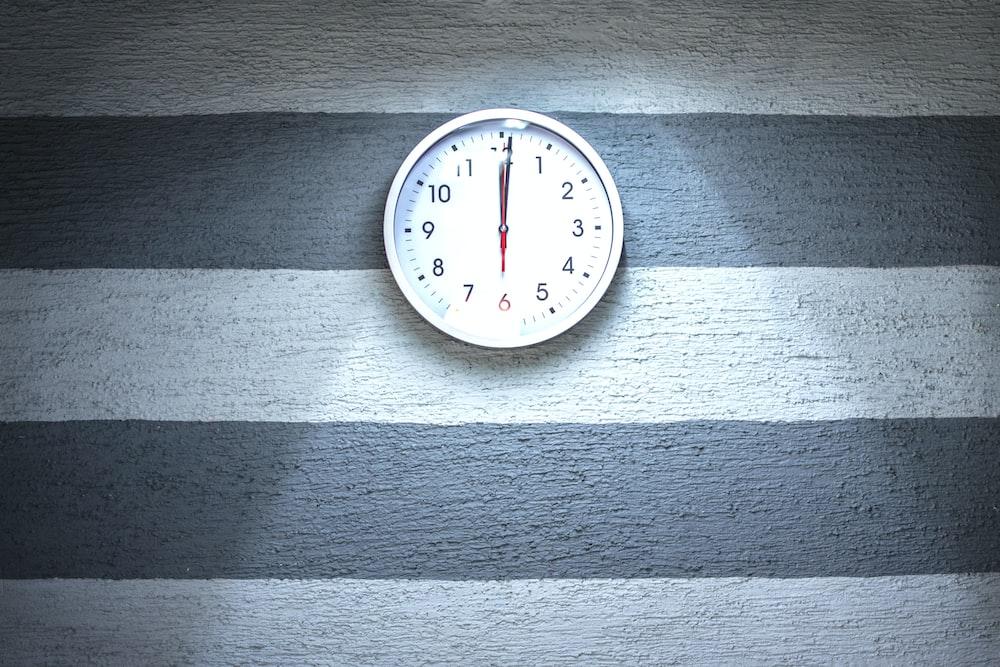 white analog wall clock reading at 12L00