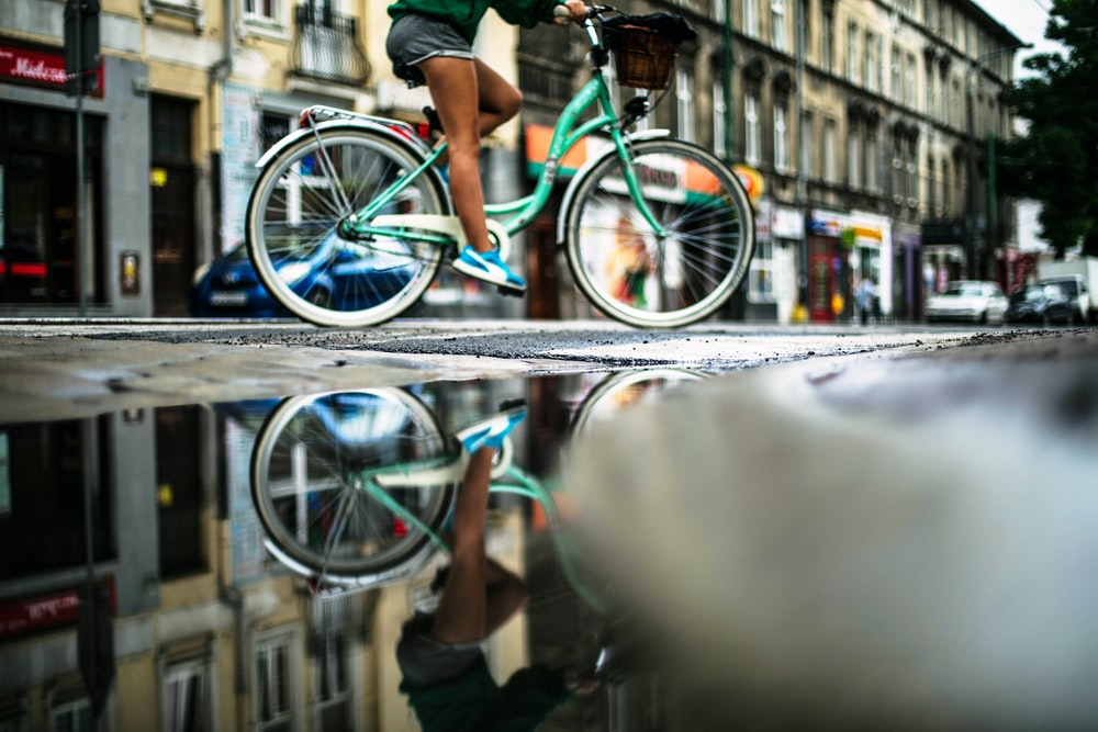person riding on teal dutch bicycle