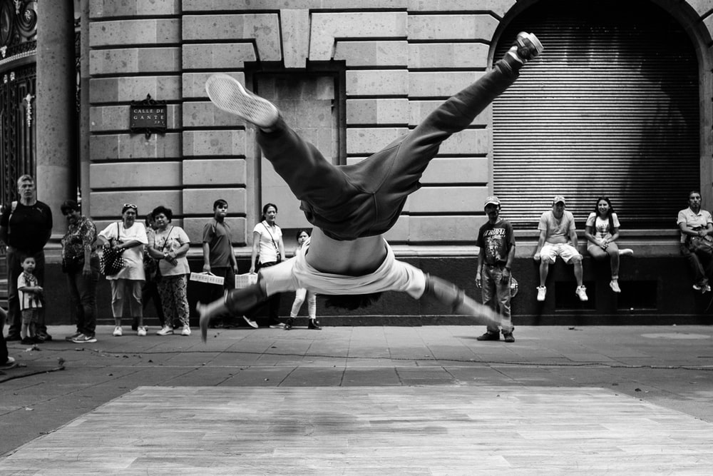 jumping man in grayscale photography