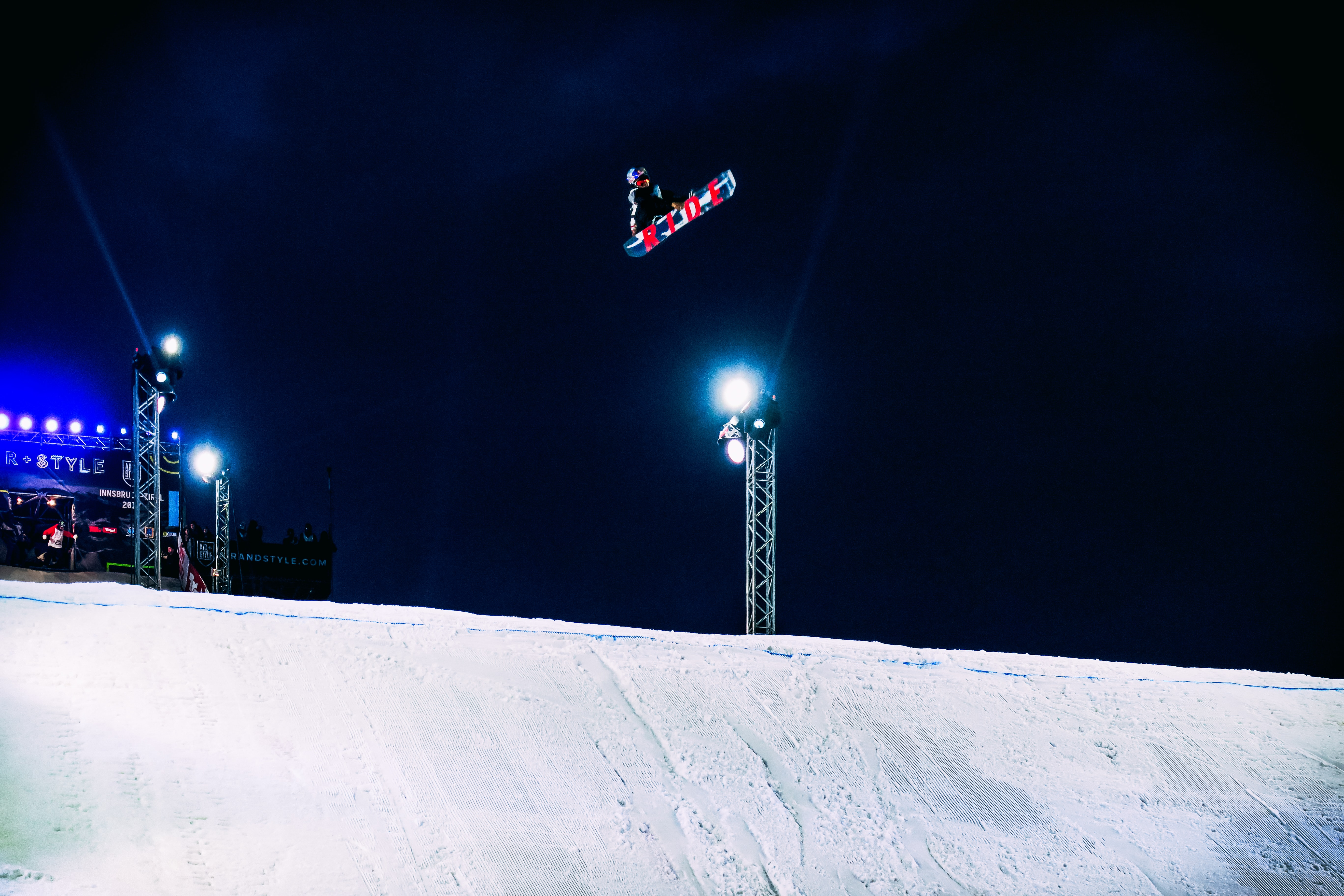 person on snowboard jumping above ramp