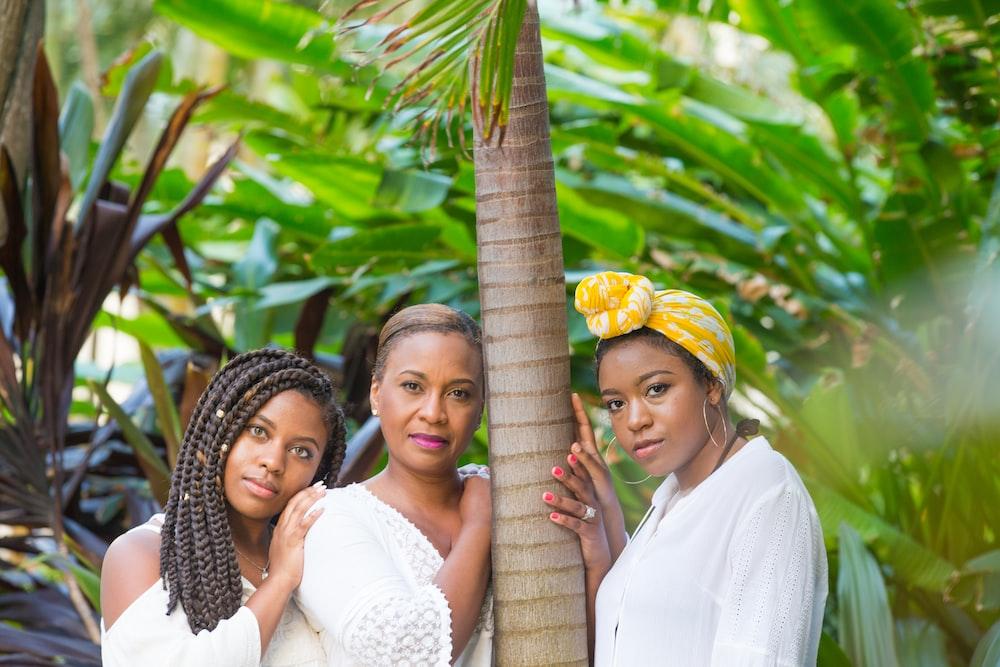 three women standing beside tree