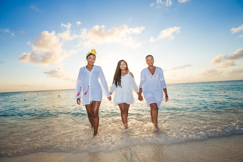 three women holding hands in seashore