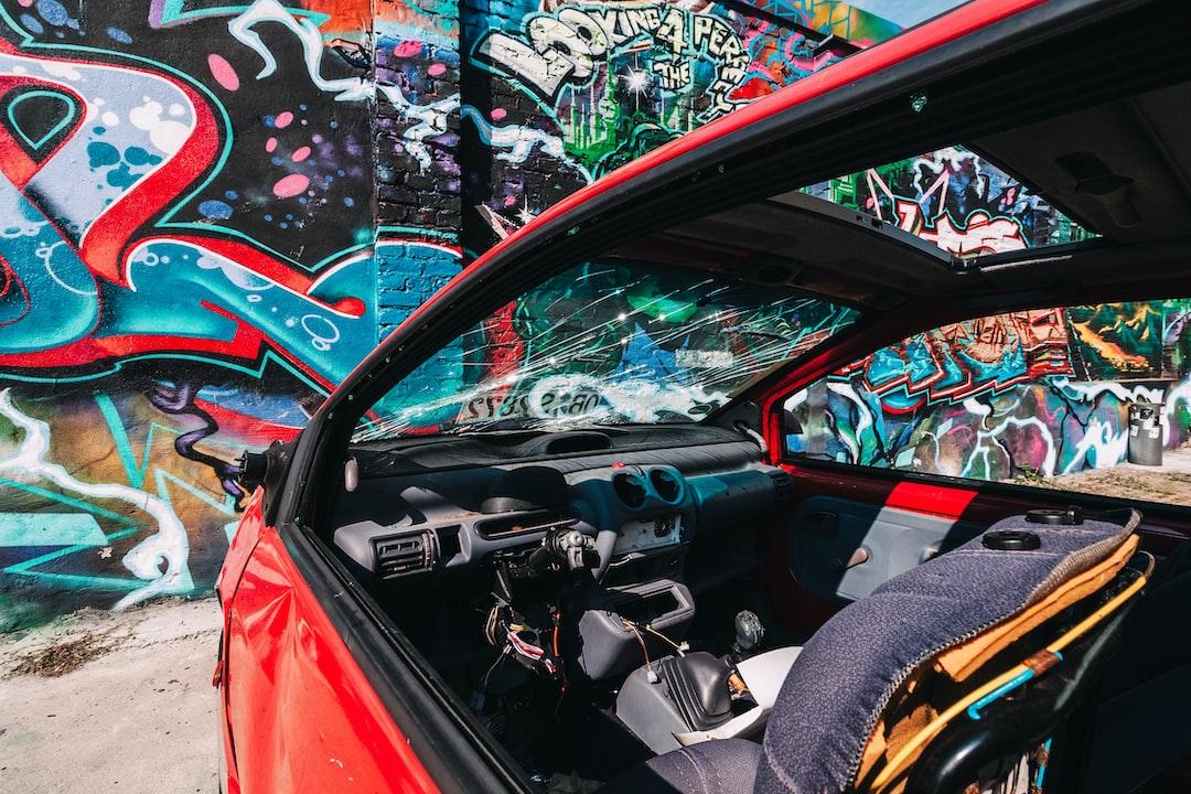 Colourful graffiti shot through a decaying car in a yard in Berlin.