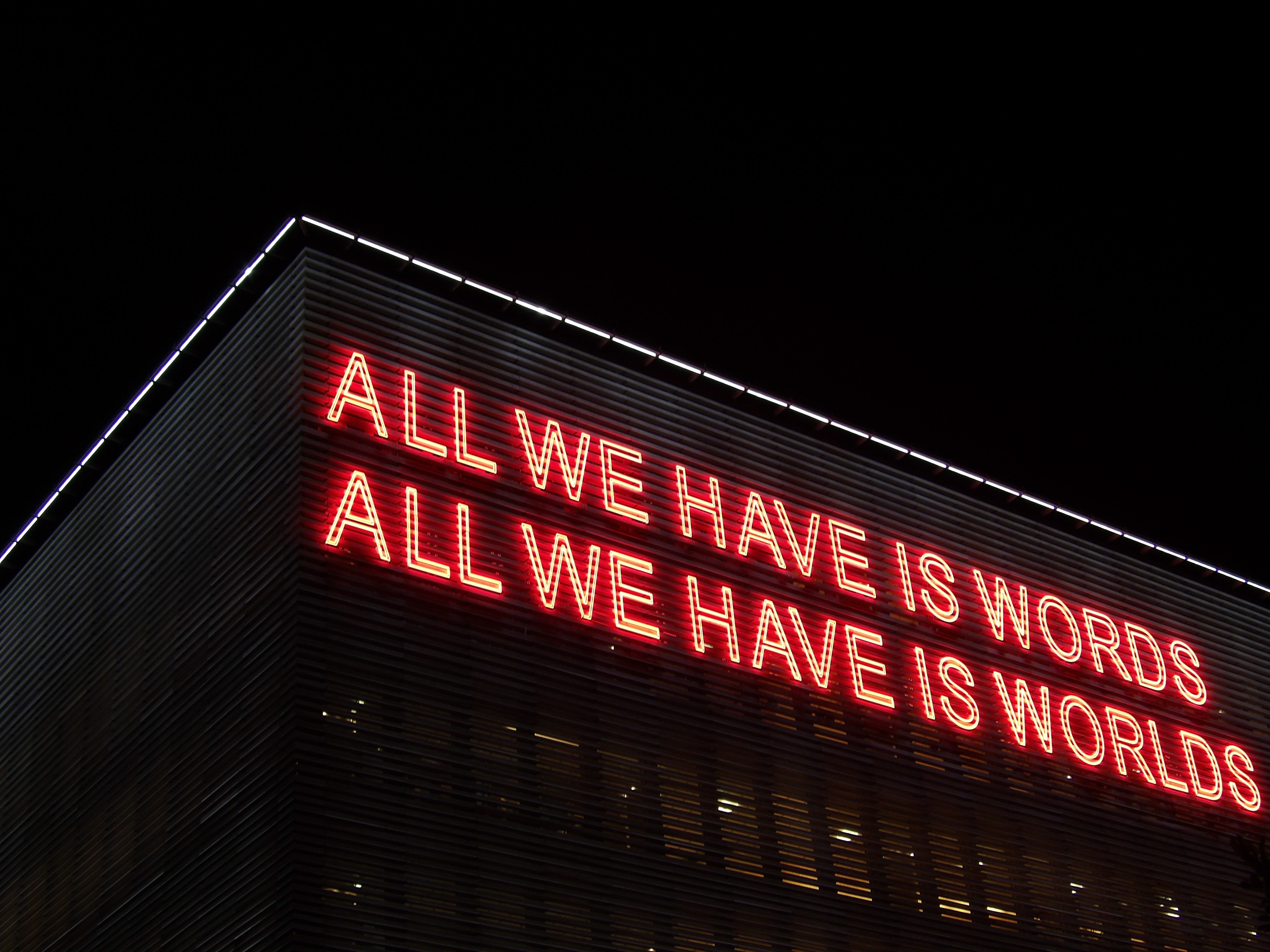 All We Have Is Words All We Have Is Worlds lighted signage at night