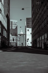silhouette of person standing on road between buildings