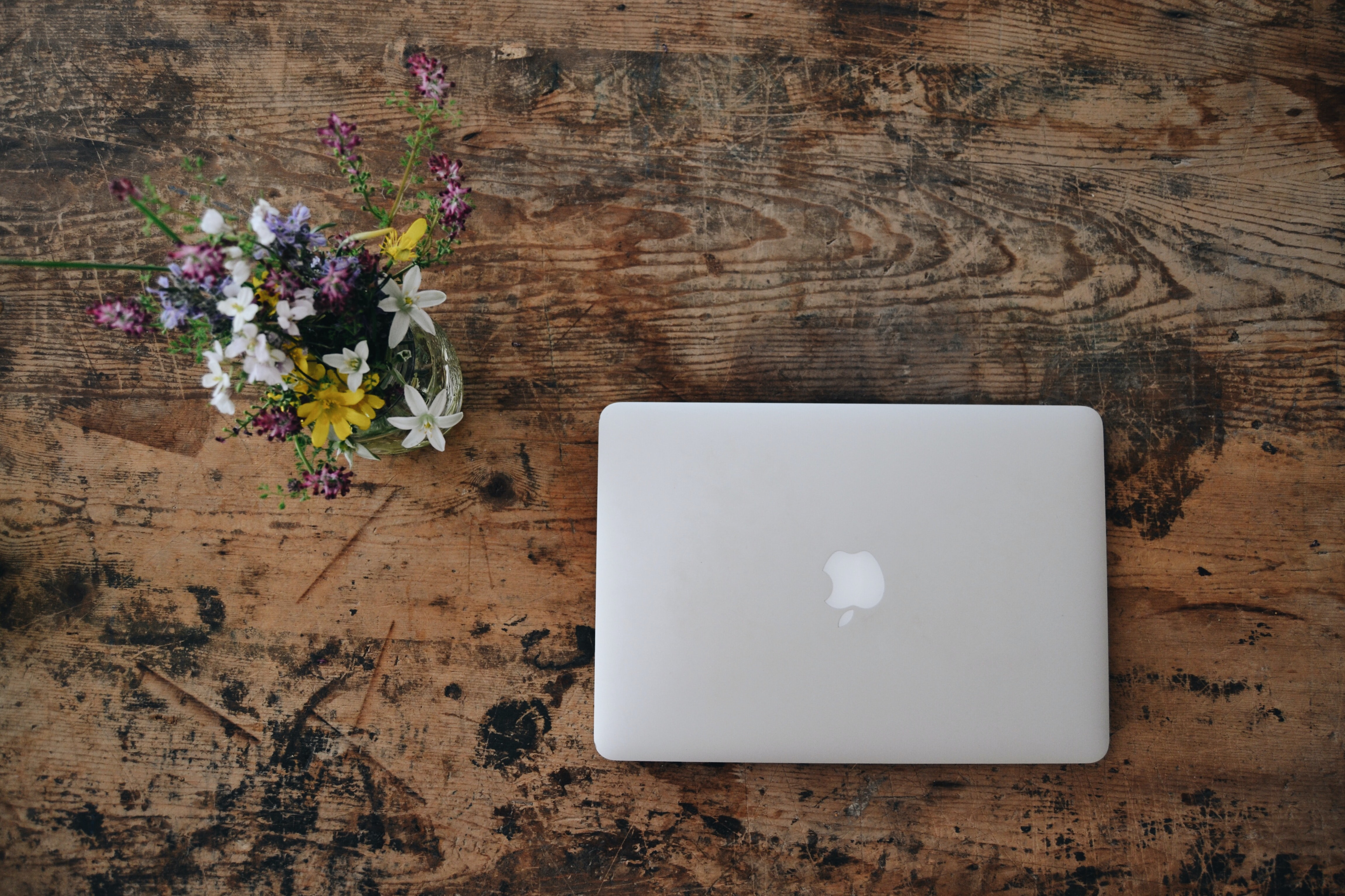 white MacBook on brown wooden surface