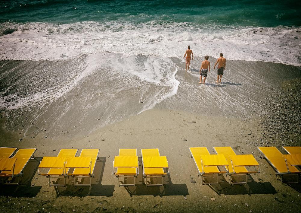 three people walking in seashore