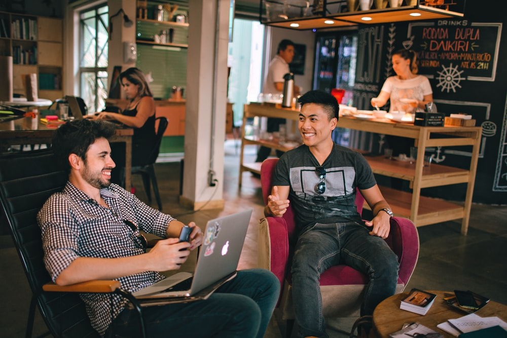 two men laughing white sitting on chairs